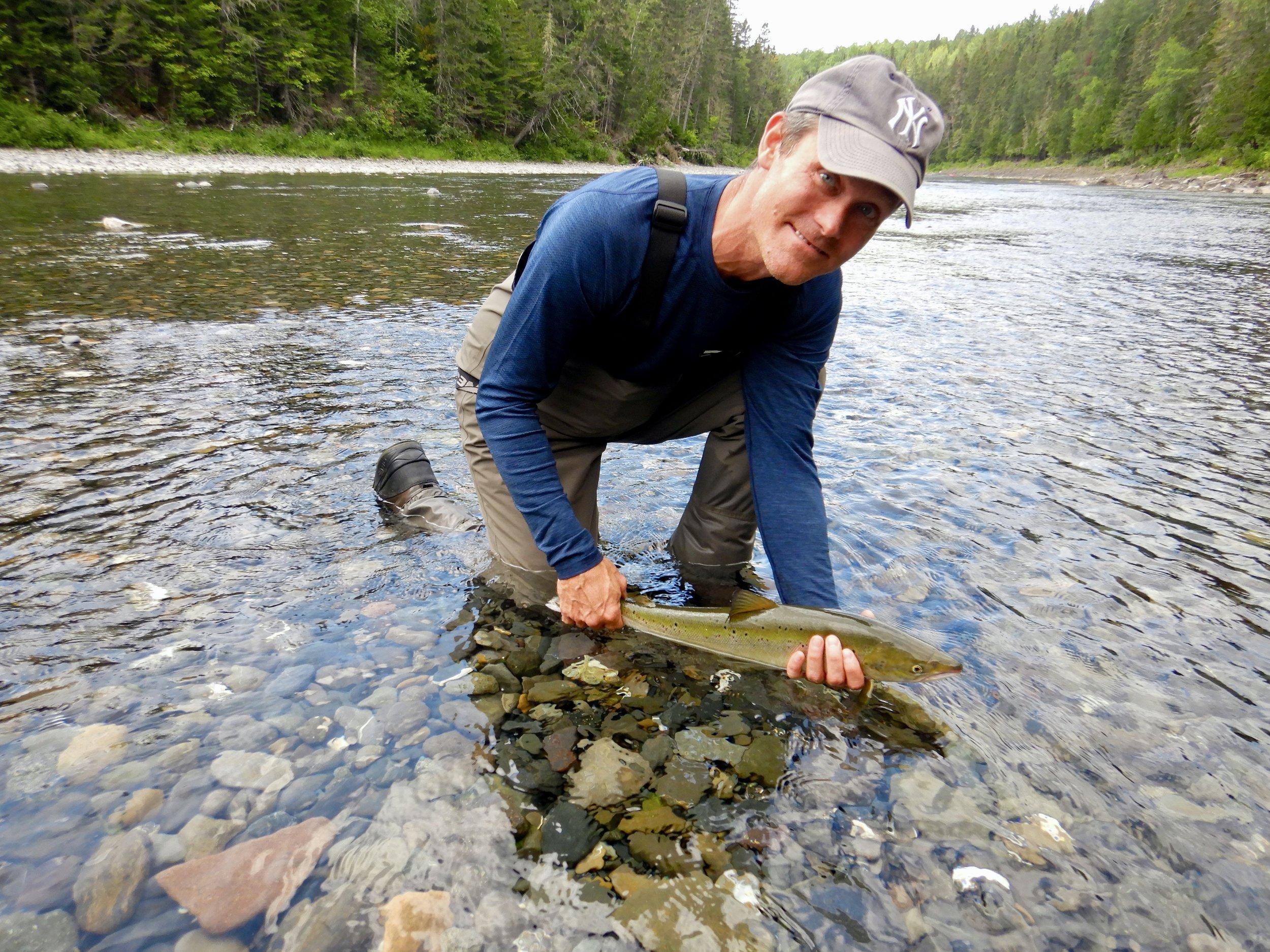Kris Heinrichs ne fait que commencer à pratiquer la pêche à la mouche, mais le voici qui, dès le premier jour, capture un madeleineau qu'il s'apprête à remettre dans la rivière Bonaventure!