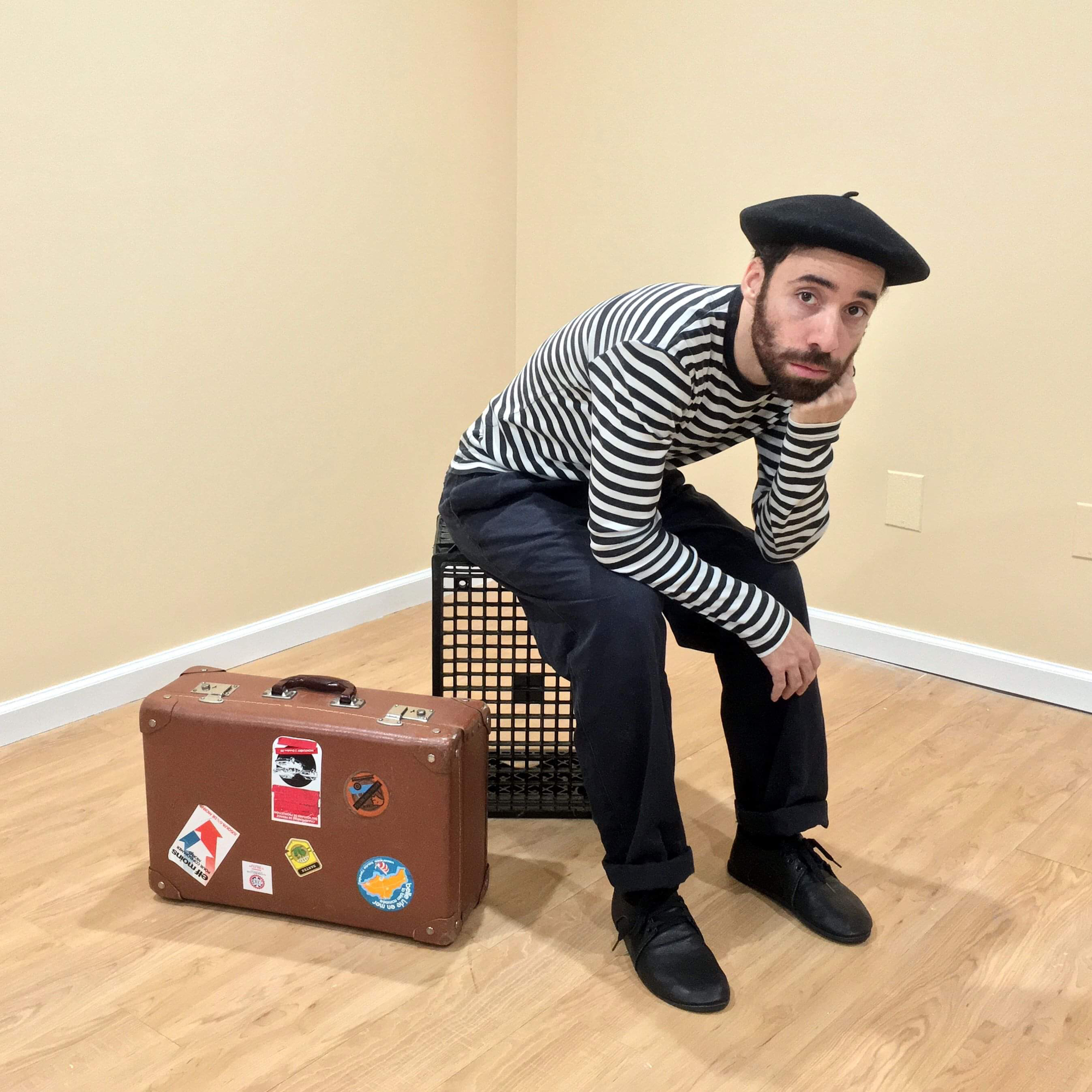 Michael sitting on crate with suitcase - web.jpg