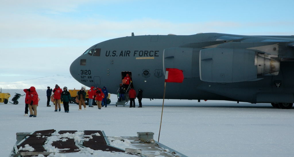 Scientists emerge on the sea ice from a C-17 Globemaster III after their flight from Christchurch, New Zealand to McMurdo Station.