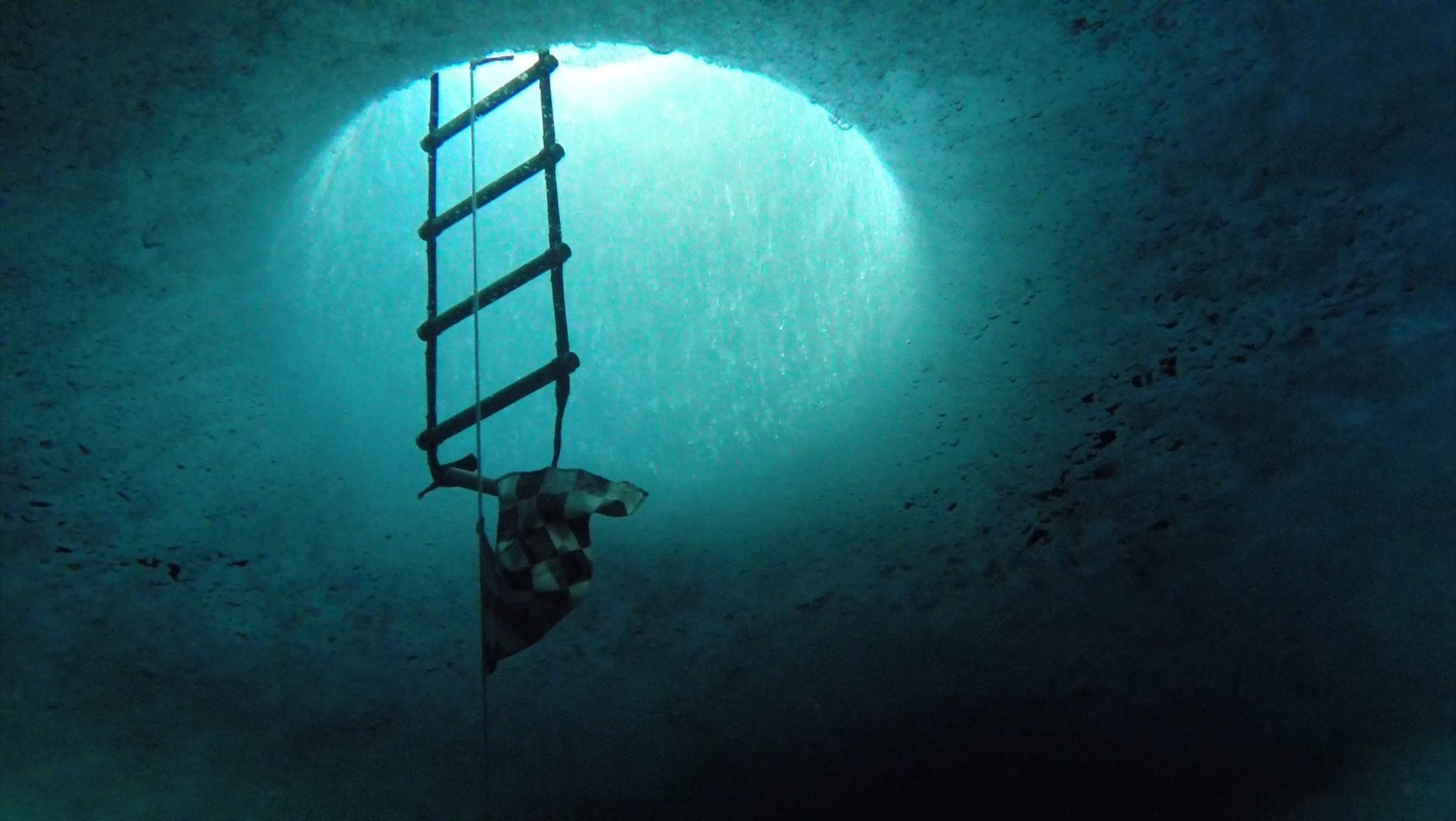 Dive hole from under the ice. The ice around McMurdo Station is approximately 6 ft thick and must be drilled through with a giant ice auger.