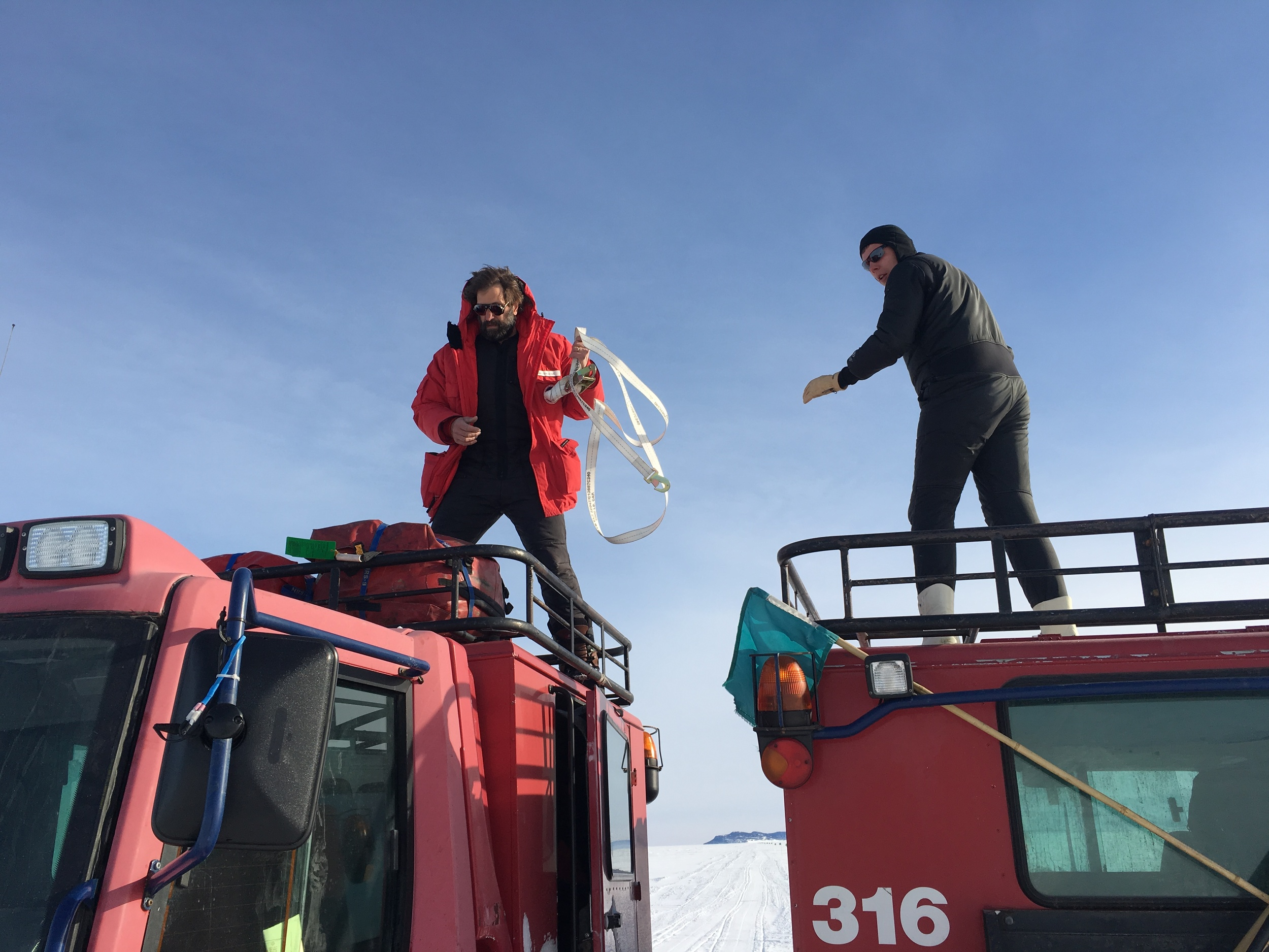 Steve and Bret transfer survival bags from one pisten bully to another out on the ice.