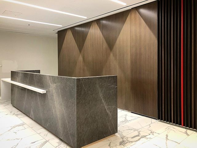 Reception Desk. Happy Easter! 🐰 . . Main Panels: Grey Stoned granite @ciot.toronto . White waterfall extension: Blizzard #2141 #caesarstone . .  #countertop #kitchen #kitchencountertop #vanity #washroom #bathroom #commercial #residential #bars #fireplace #fireplacesurround #tubdeck #marble #granite #quartz #quartzite #design #interiordesign #cabinet #home #luxury @caesarstoneca @caesarstoneus