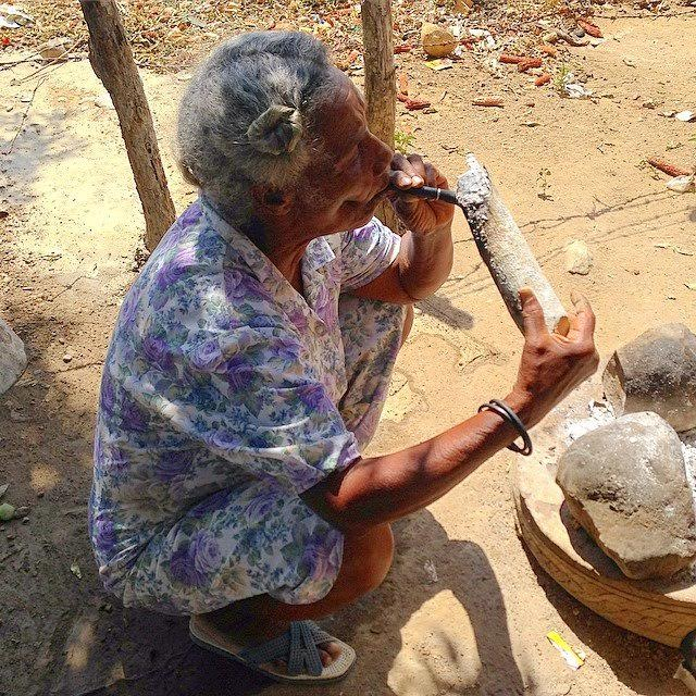 Dominican Abuela lighting her cigar with burning wood directly from the fire used to cook the daily lunch of rice, beans, and if you're lucky, a little meat.