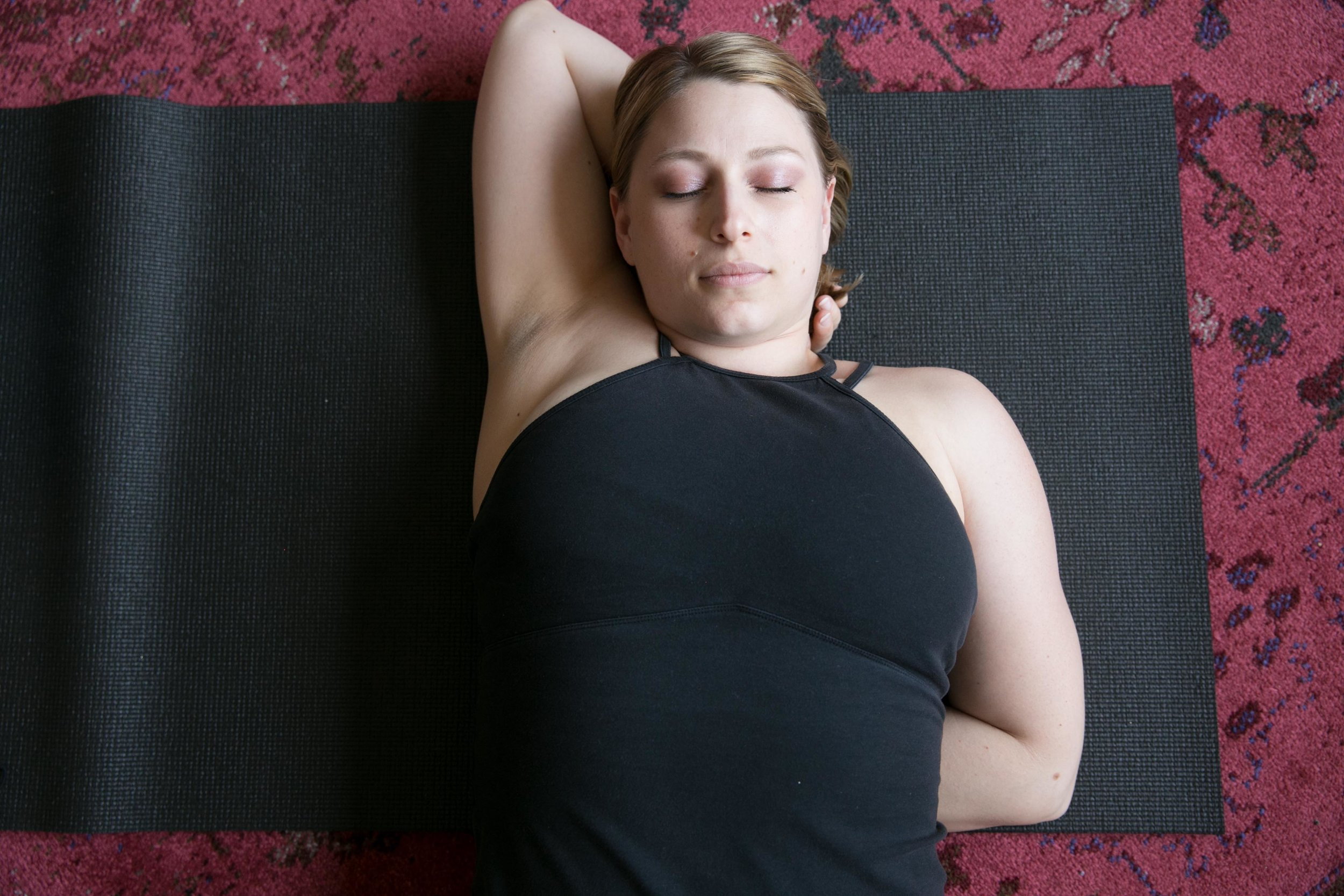 Reclining gomukhasana - Roll over onto your back (on top of your lower forearm.) Use your top hand as a pillow, and keep your feet flat on the ground at first to support your low back. Stay until you feel the tension in your bottom shoulder beginning to melt.To go deeper: stretch your legs out straight. Challenge yourself:deepen your breath without tensing your neck and jaw.