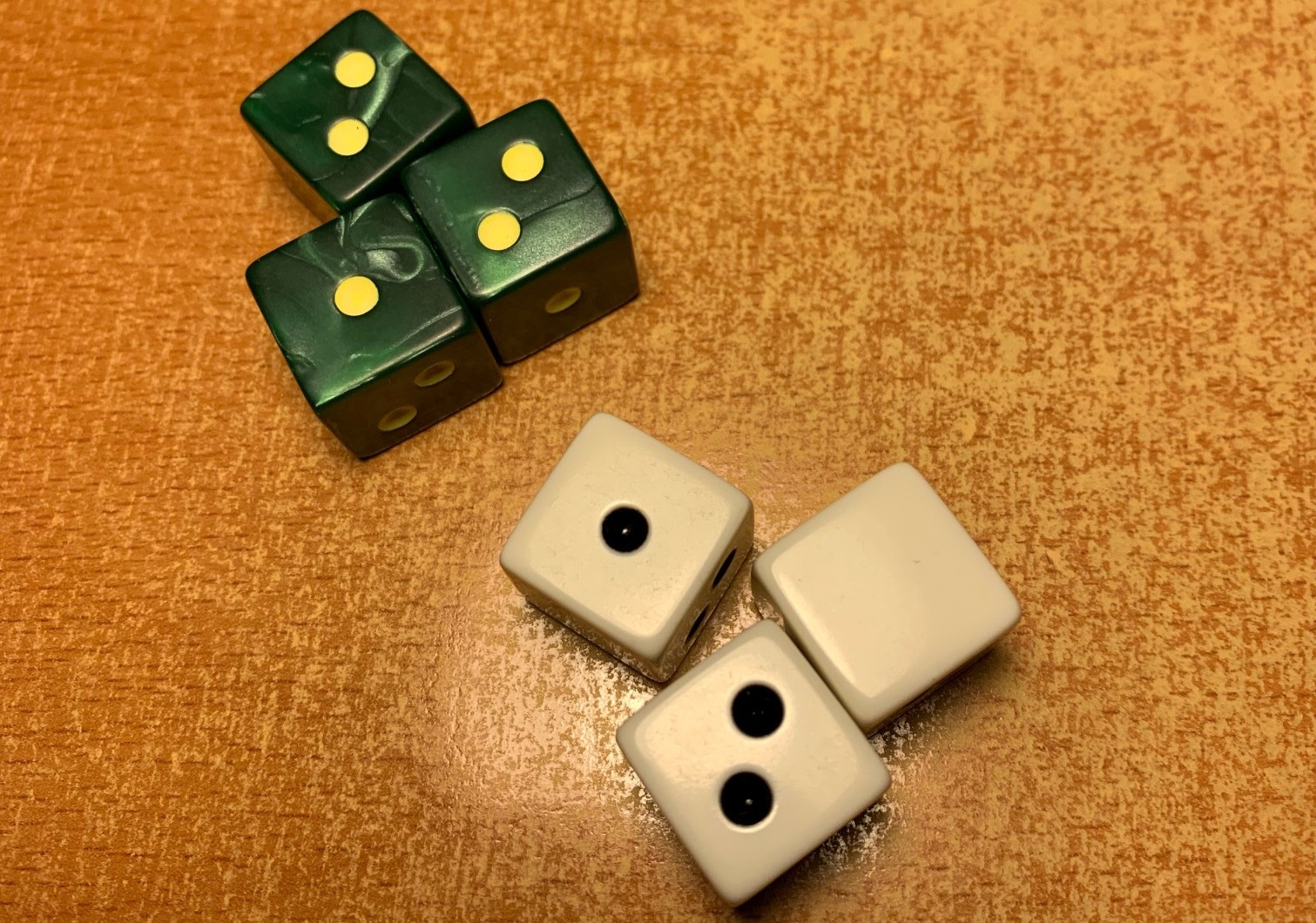 Premium pearlescent green die with yellow pips vs. the standard bones
