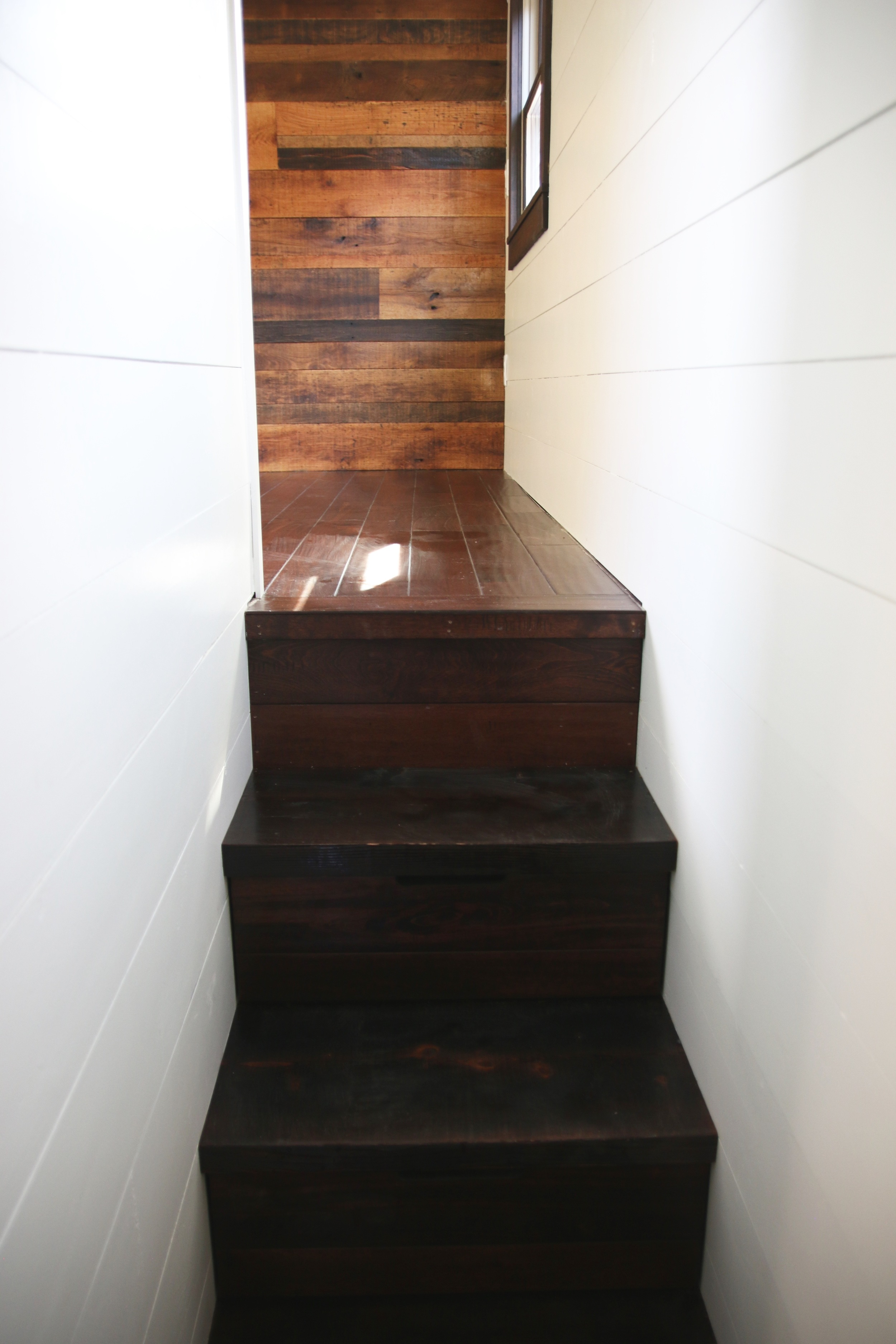 The Phoenix by Wind River Tiny Homes. Storage stairs leading to the bedroom above the gooseneck.