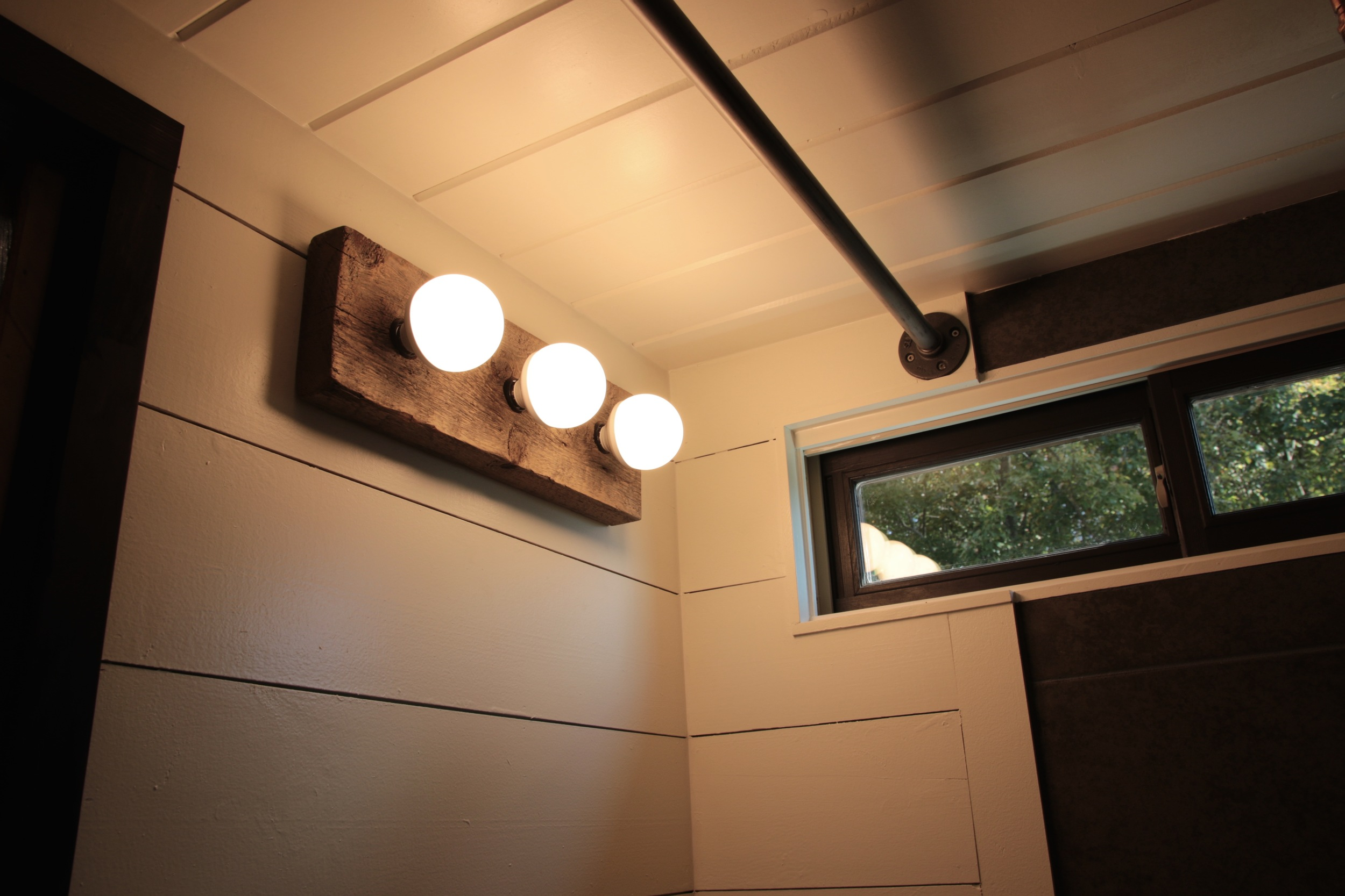 The Phoenix by Wind River Tiny Homes. Custom made barn wood vanity light.