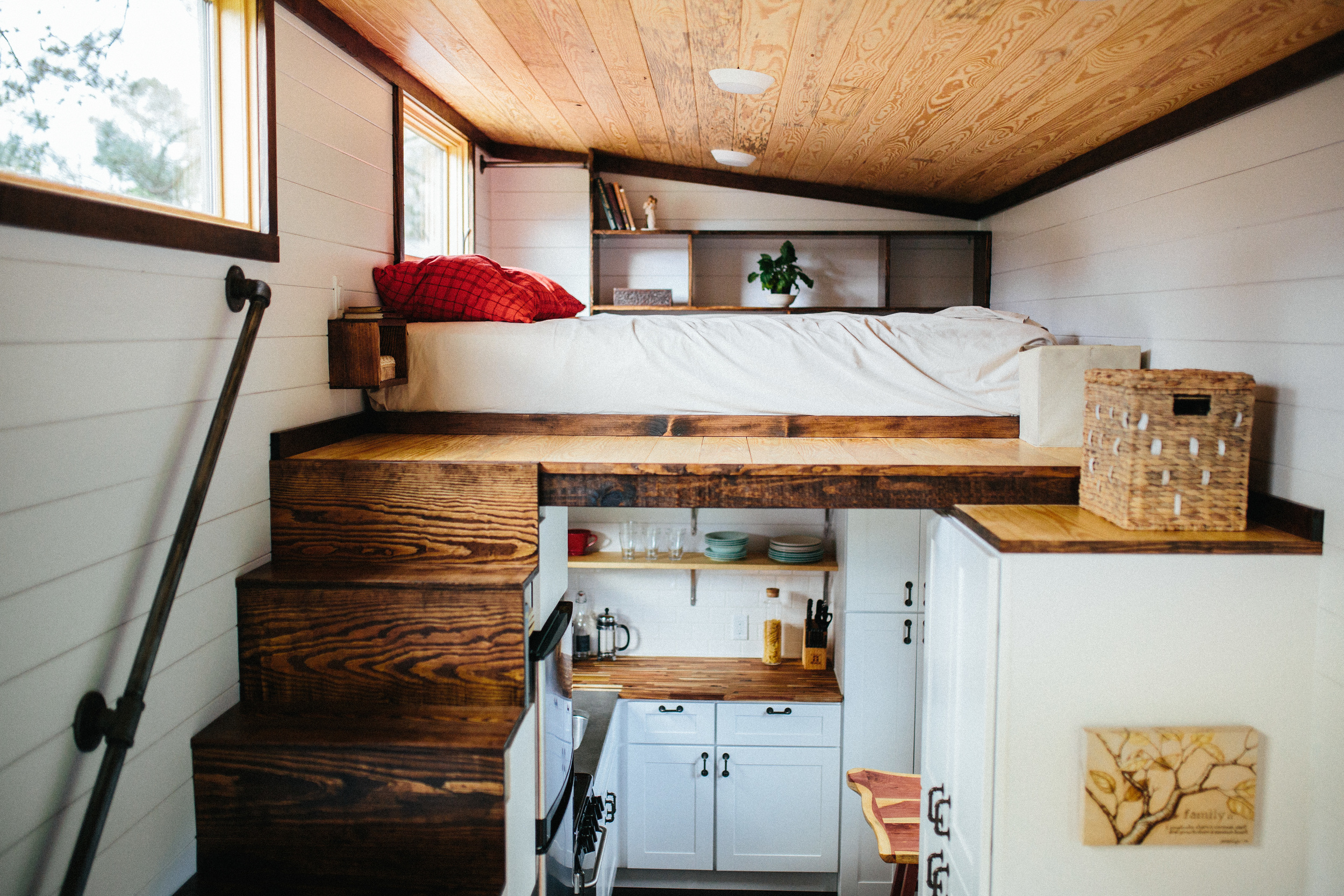 The Chimera by Wind River Tiny Homes. Storage stairs with stained treads up to main loft, built in nightside tables, welded rod handrail and clothing rail, built in cubbys.