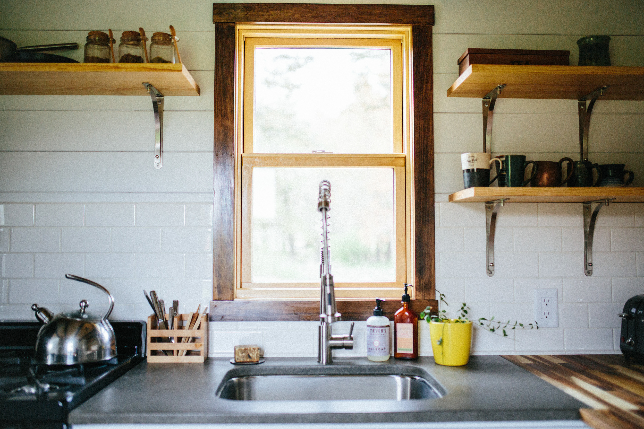 The Chimera by Wind River Tiny Homes. Concrete and butcher block countertops, open shelving, subway tile backsplash.