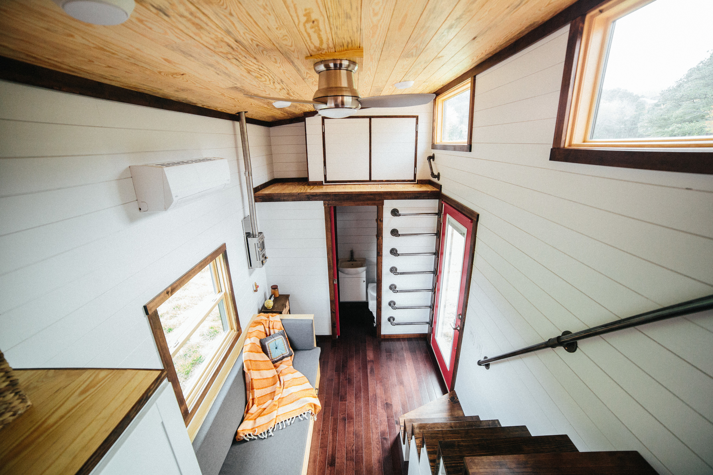 The Chimera by Wind River Tiny Homes. looking down from loft into living room and bathroom.