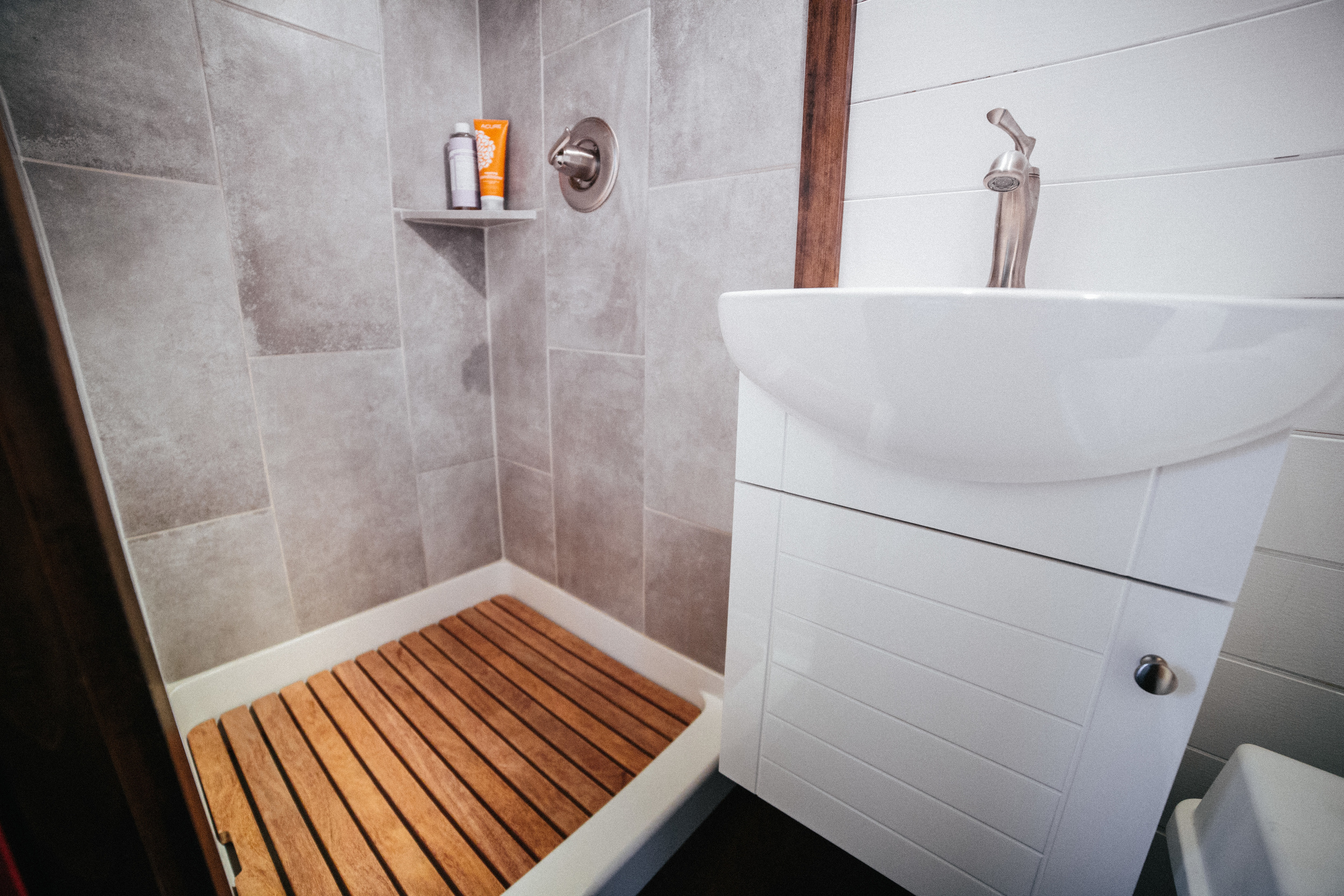 The Chimera by Wind River Tiny Homes. Tiled shower with custom wood showerpan and small vanity.