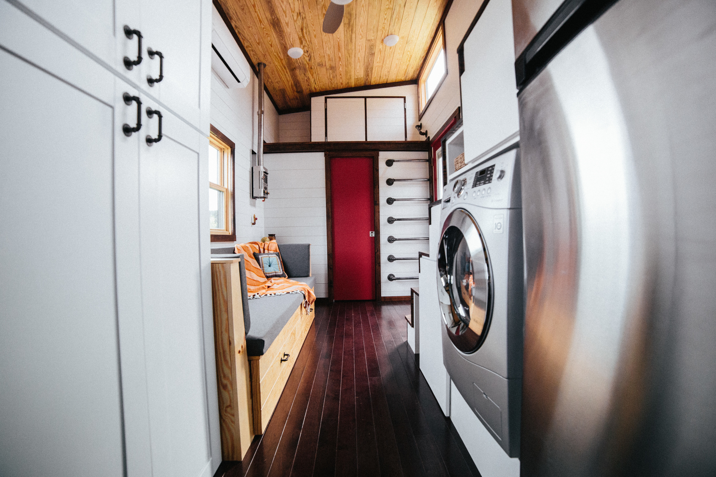 The Chimera by Wind River Tiny Homes. Clothing closet, custom built in couch that slides out for a bed and lifts for storage, bathroom at the end with storage loft, storage stairs.