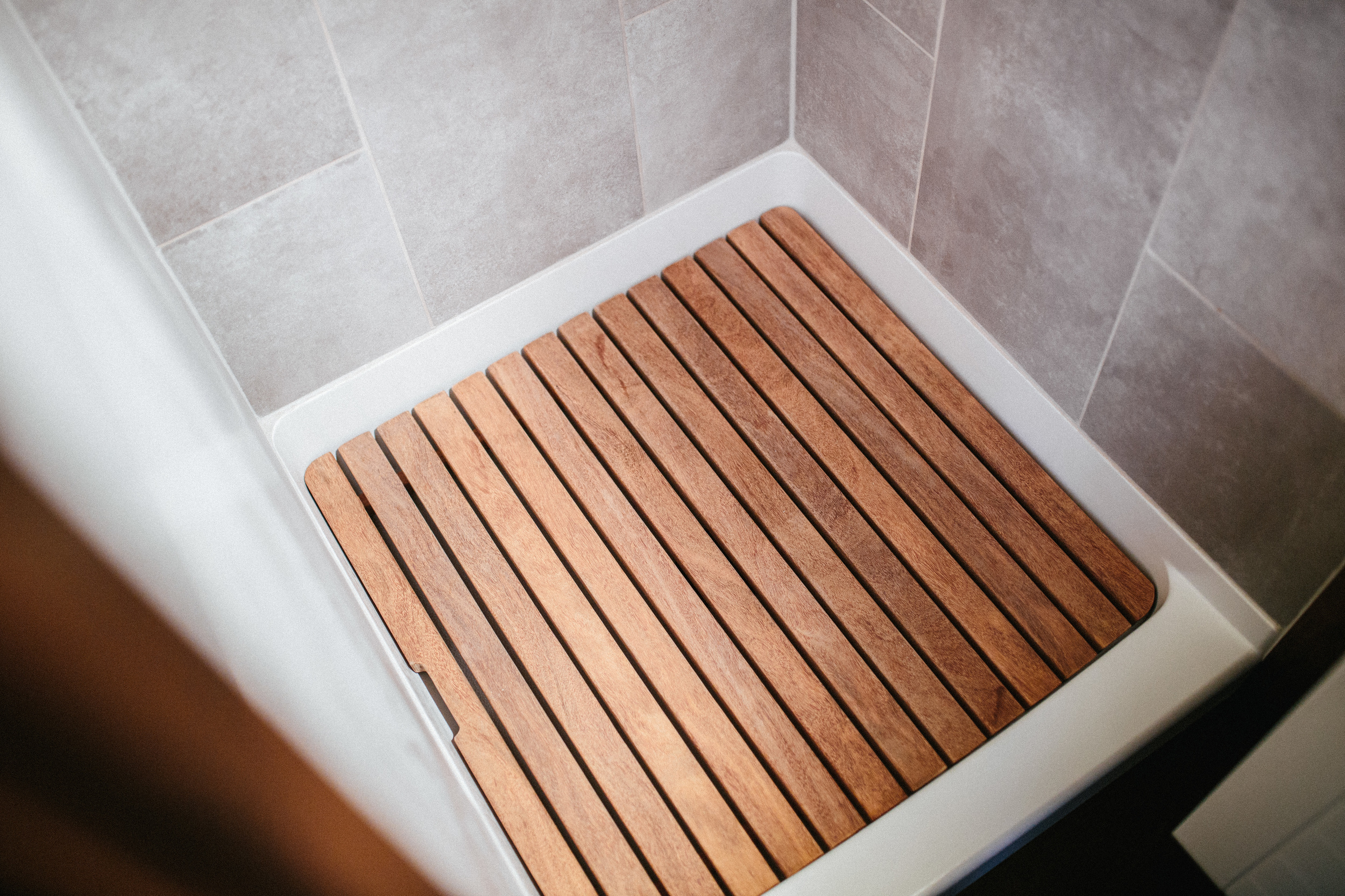 The Chimera by Wind River Tiny Homes. Tiled shower with custom wood showerpan.