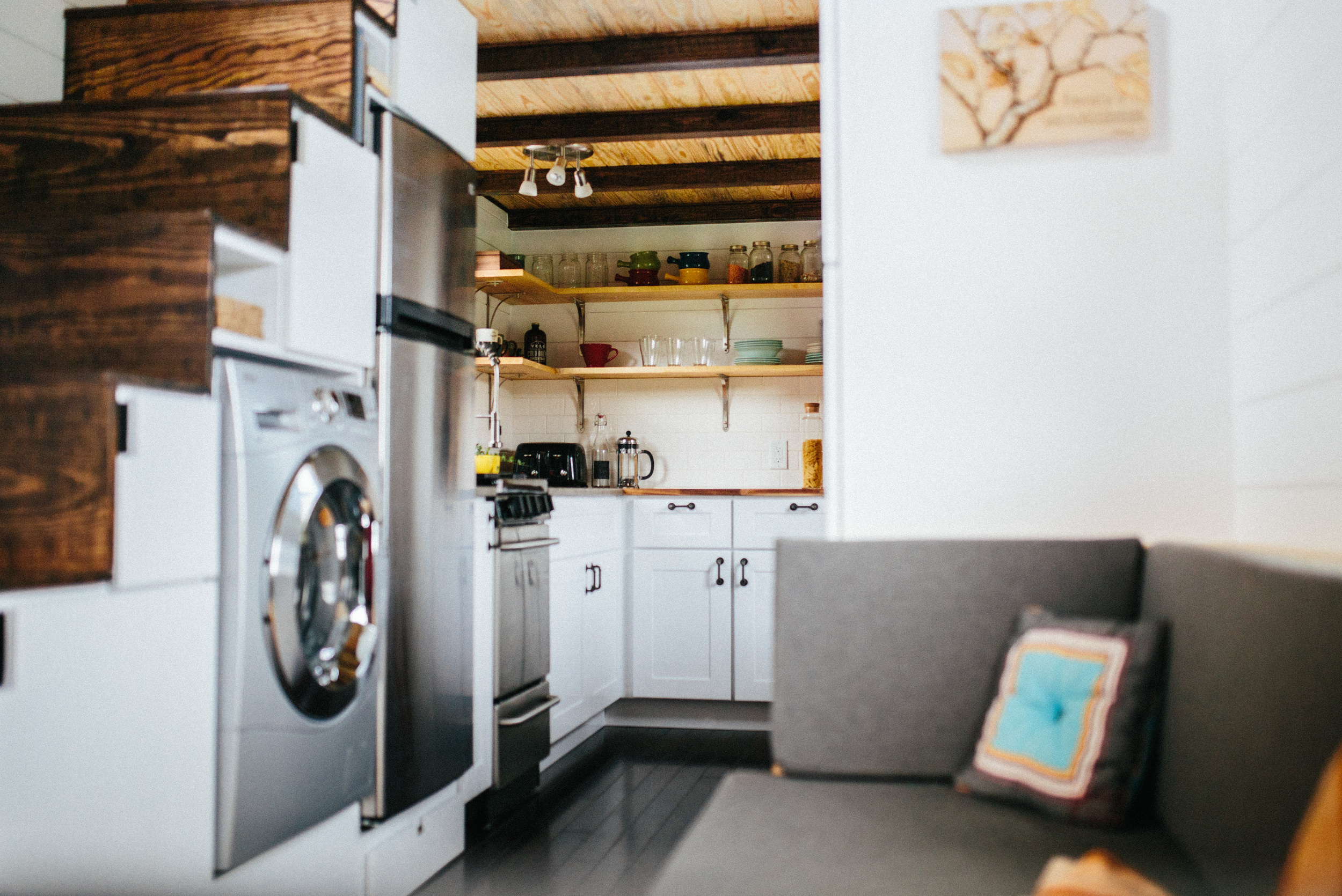 The Chimera by Wind River Tiny Homes. Custom storage stairs with Combo W/D.