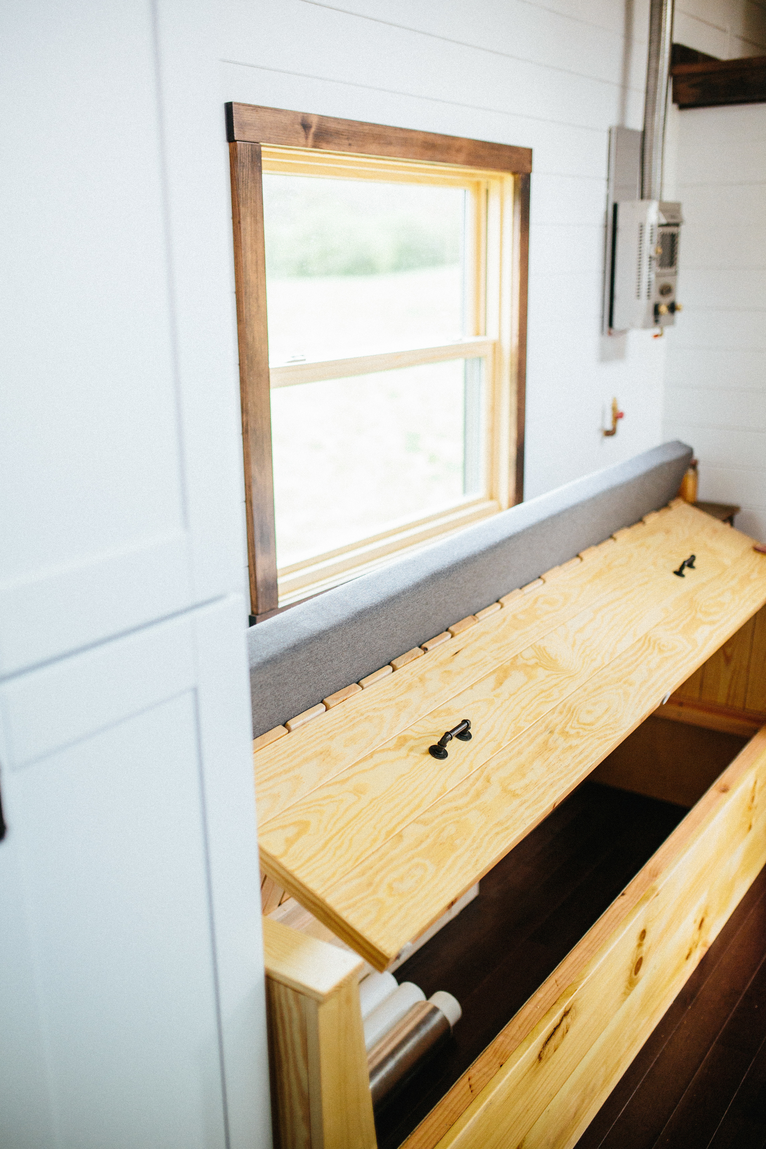 The Chimera by Wind River Tiny Homes. Custom built in couch that slides out for a bed and lifts for storage.