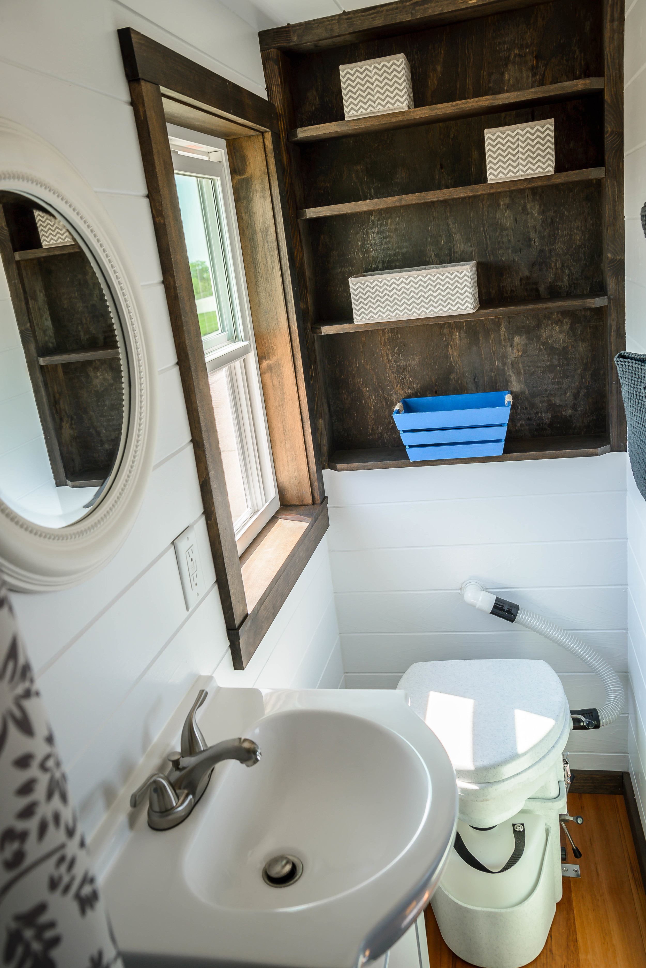 The Triton by Wind River Tiny Homes. Bathroom with vanity and custom built in shelving unit.