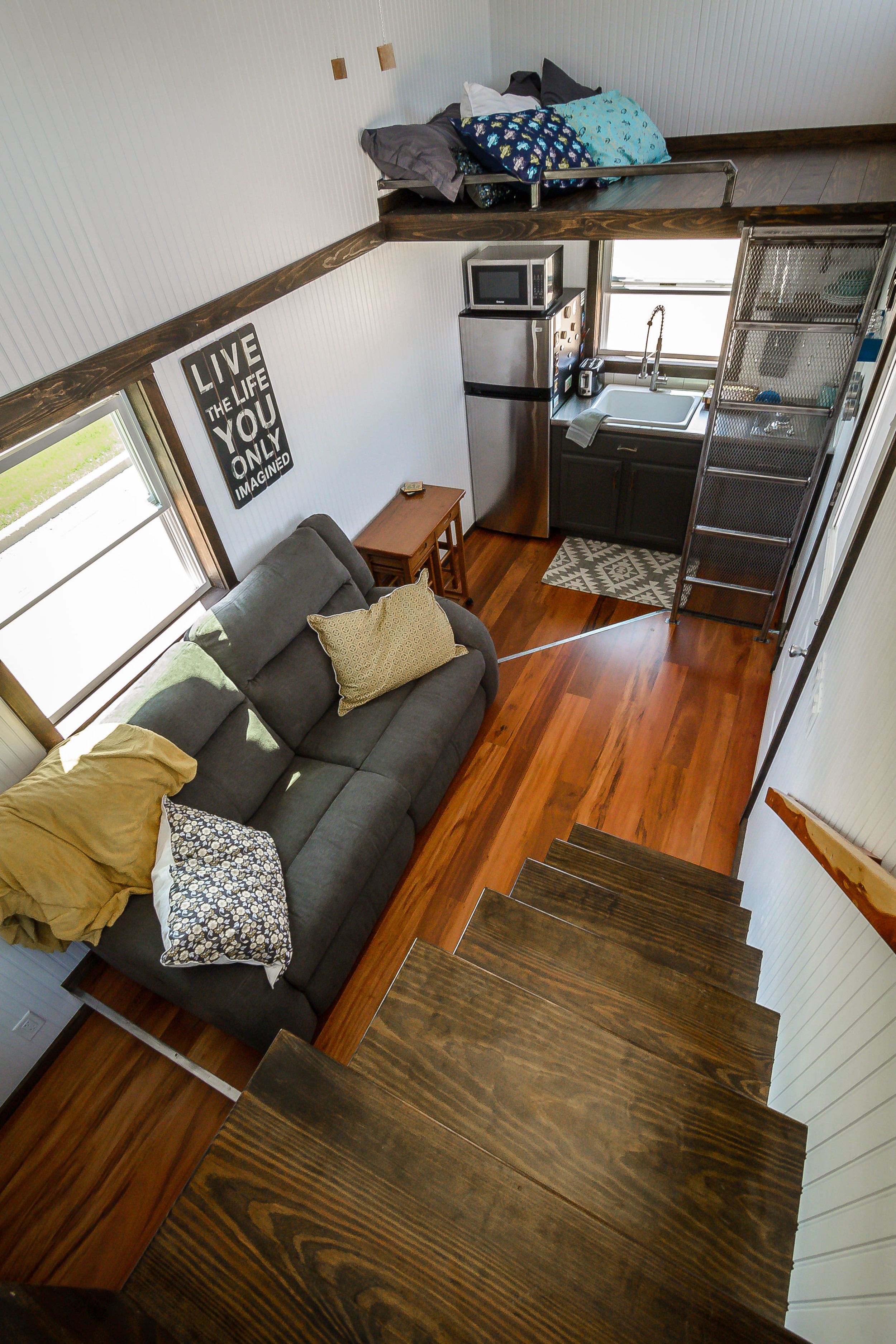 The Triton by Wind River Tiny Homes. Overview of floorplan. Custom storage stairs leading up to loft. Living space in the middle of home, with bathroom, office space, and walk in closet under loft.