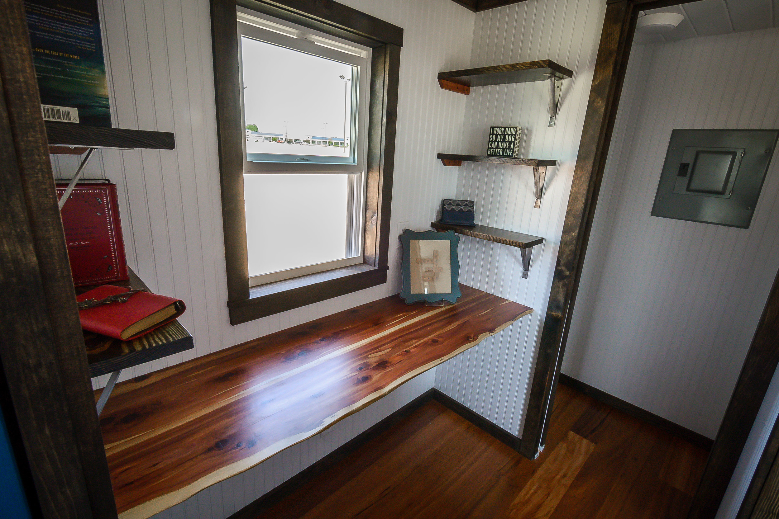 The Triton by Wind River Tiny Homes. Custom office space with built in shelves and live edge cedar desk. Pocket door into Living Room. Behind office space is walk in closet/utilities.