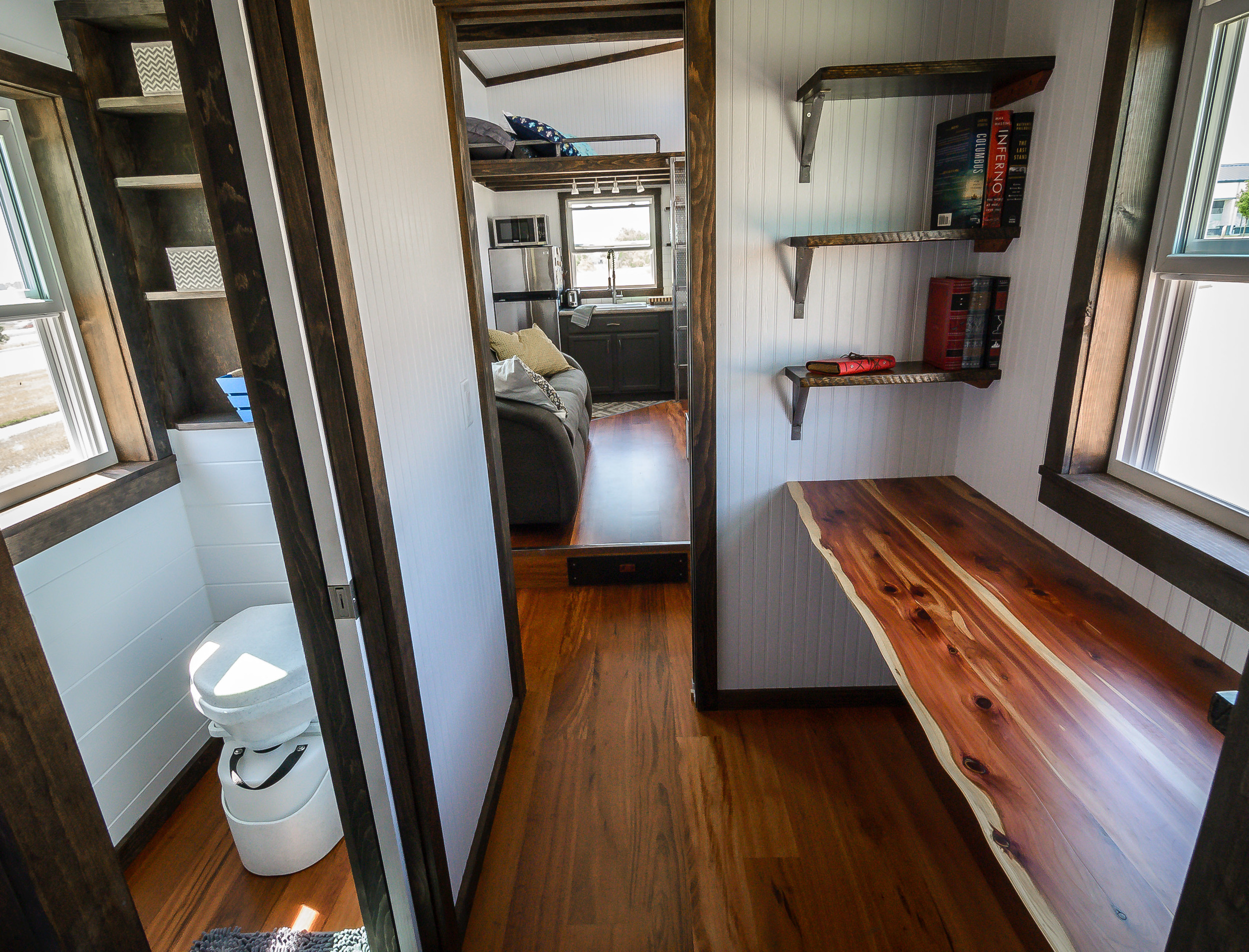 The Triton by Wind River Tiny Homes. Custom office space with built in shelves and live edge cedar desk. Pocket door leading into Living Room. Opposite desk area is bathroom with pocket door.