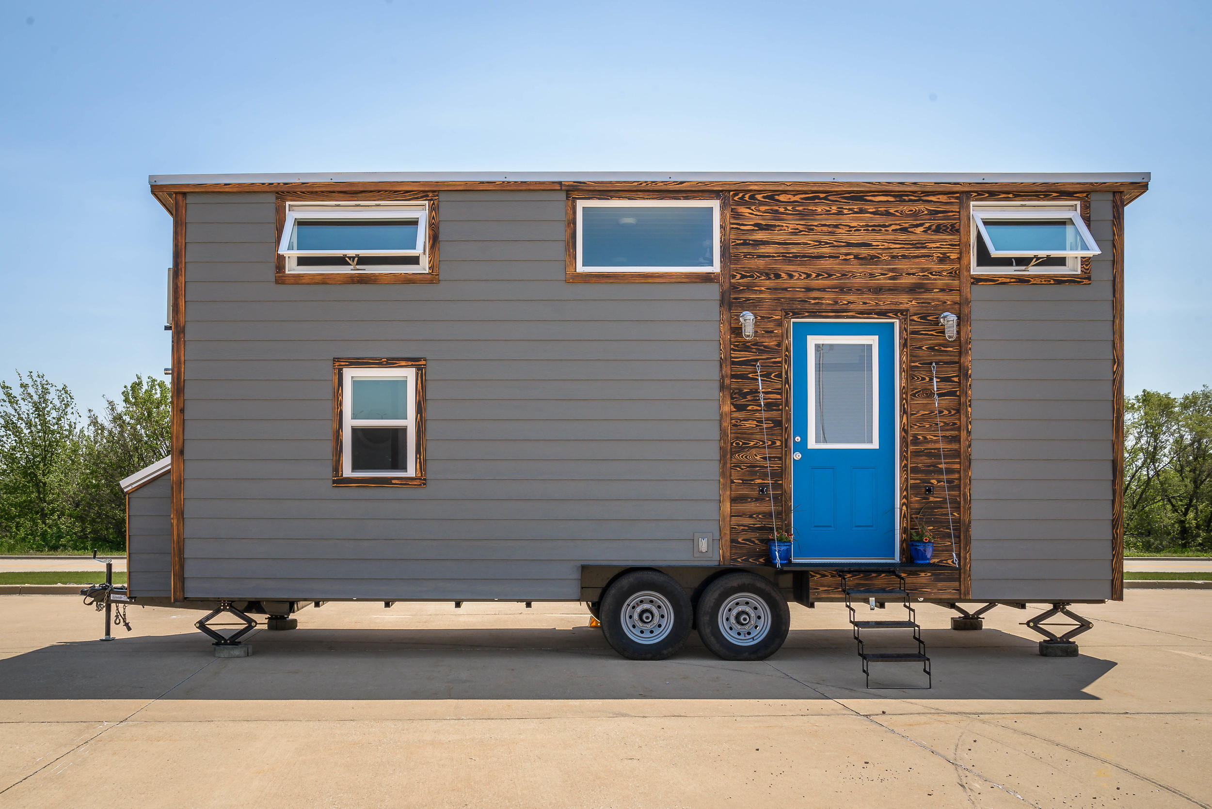 The Triton by Wind River Tiny Homes. Exterior with metal folding porch.