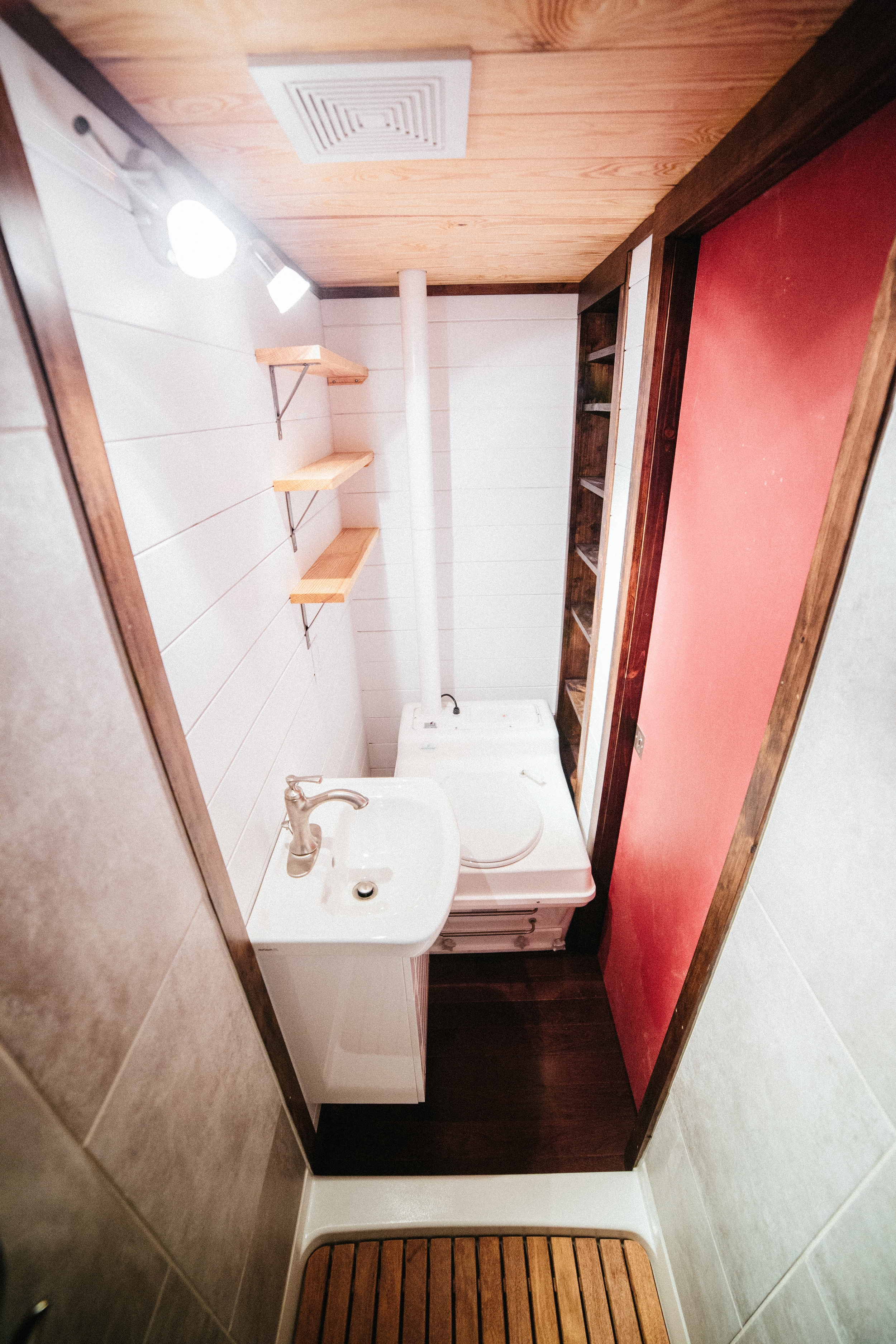 The Chimera by Wind River Tiny Homes. Vanity, toilet, open shelving, built in recessed shelving.