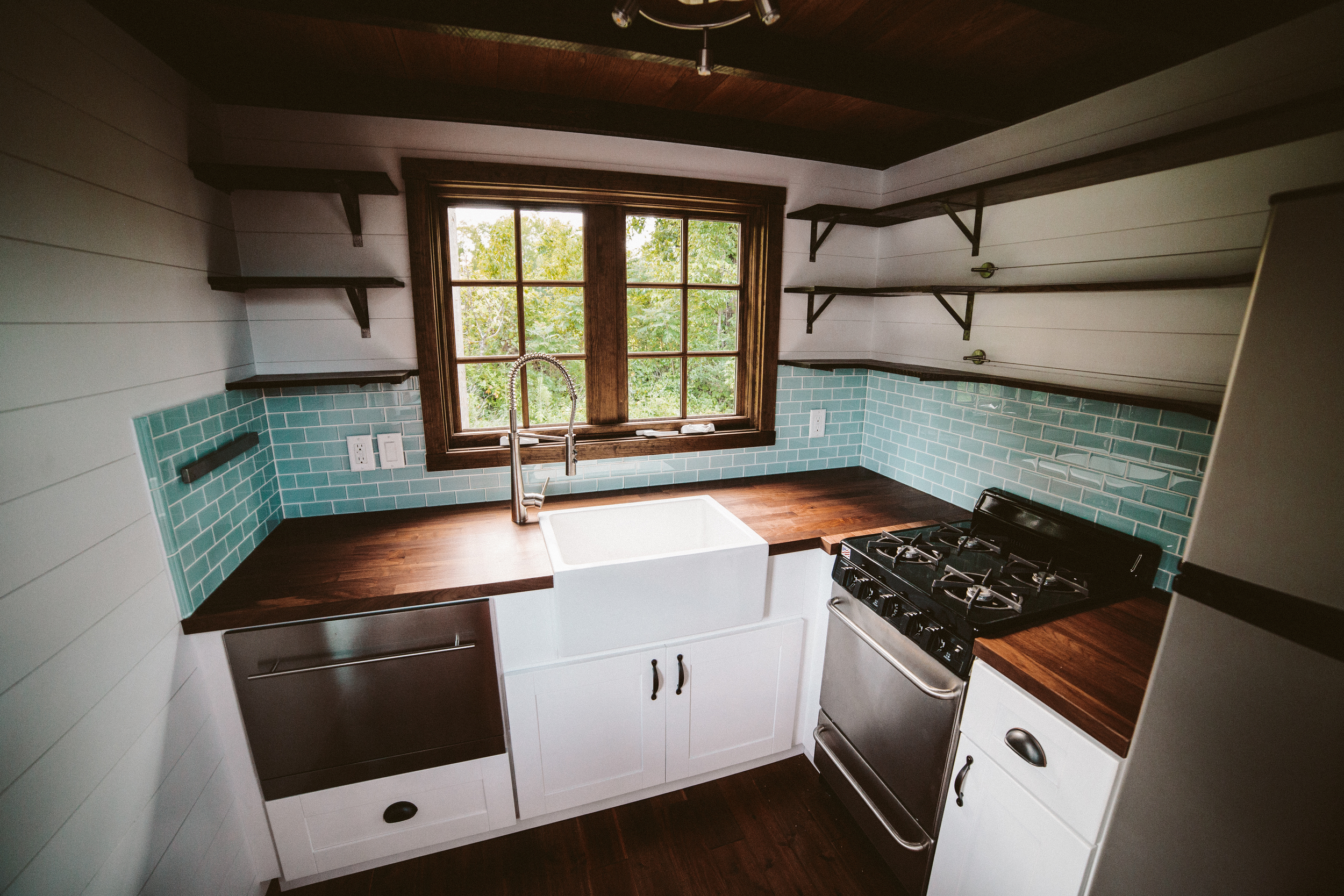 The Mayflower - Farmhouse sink, butcher block counters, custom welded open shelving, seaglass subway tile, oven, drawer dishwasher, and french casement window