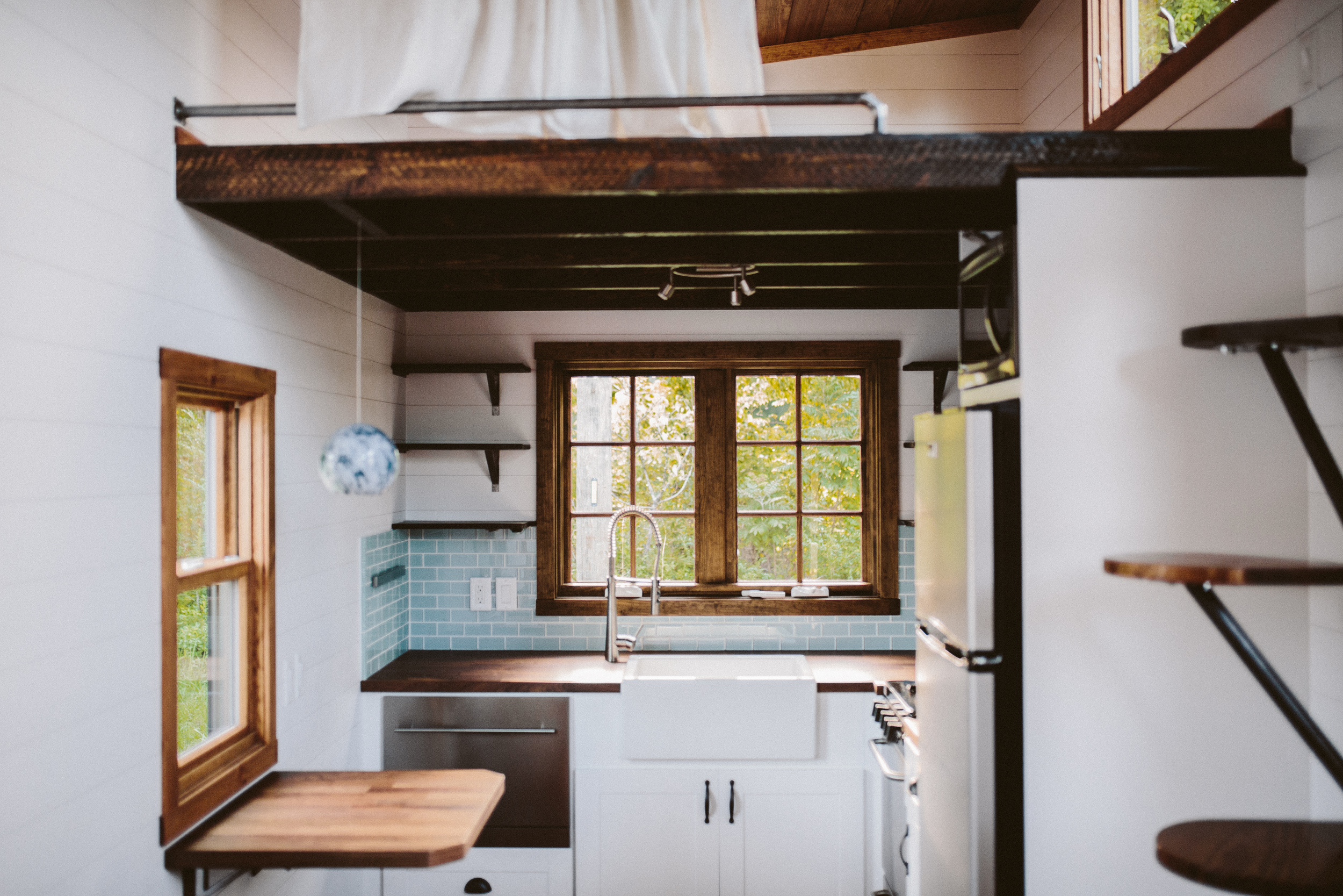 The Mayflower - Folding table, farmhouse sink, butcher block counters, custom welded open shelving, seaglass subway tile, oven, drawer dishwasher, and french casement window