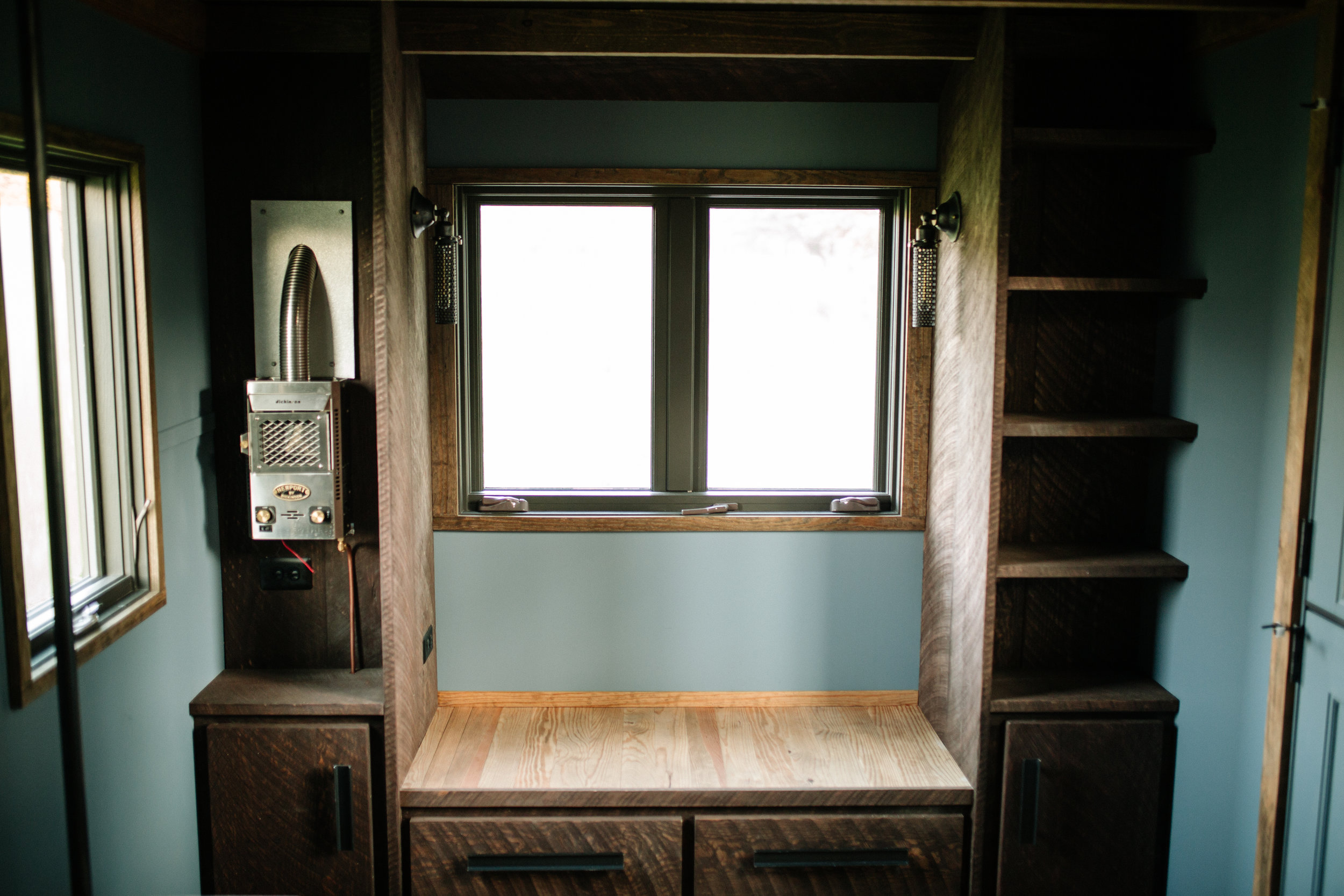 The Rook by Wind River Tiny Homes - Dickinson propane heater, built in window seat couch with built in side shelving.
