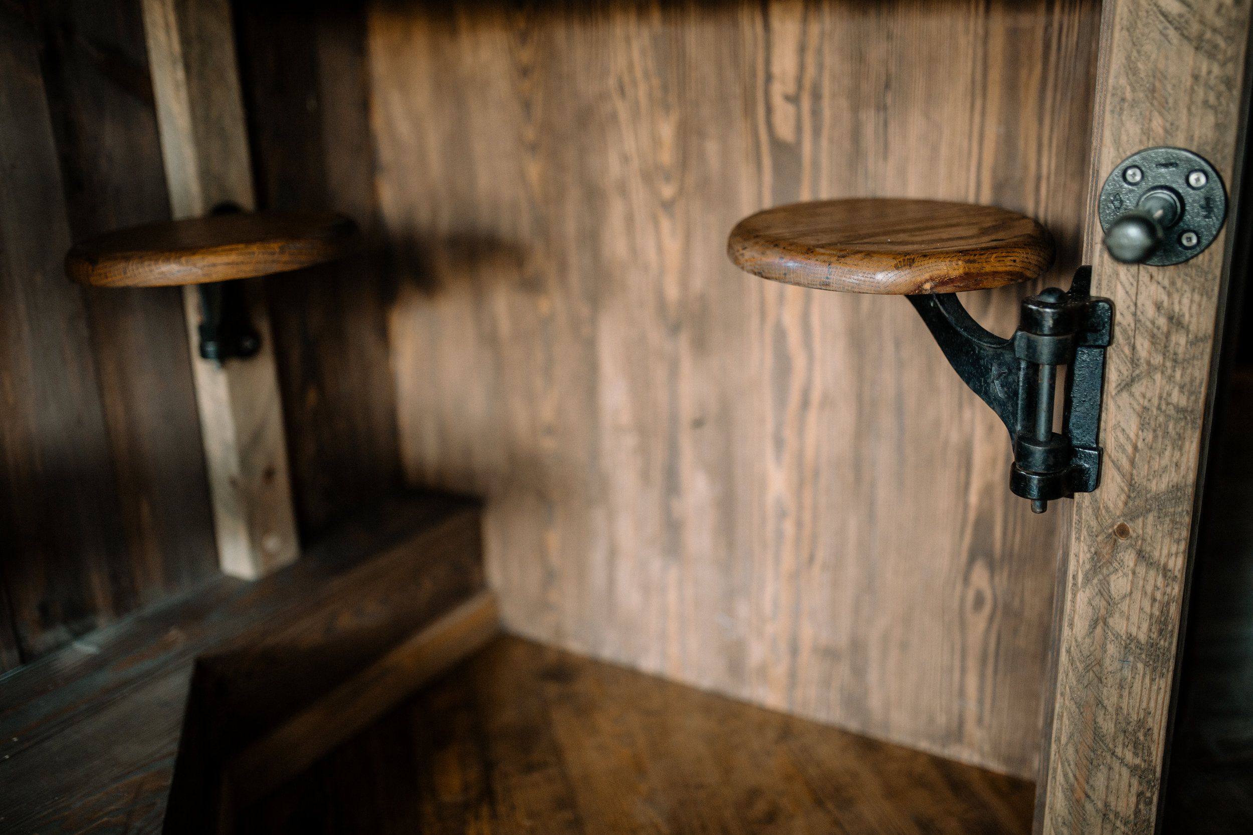 The Rook by Wind River Tiny Homes - Cast iron swivel swing in stools with wooden tops.