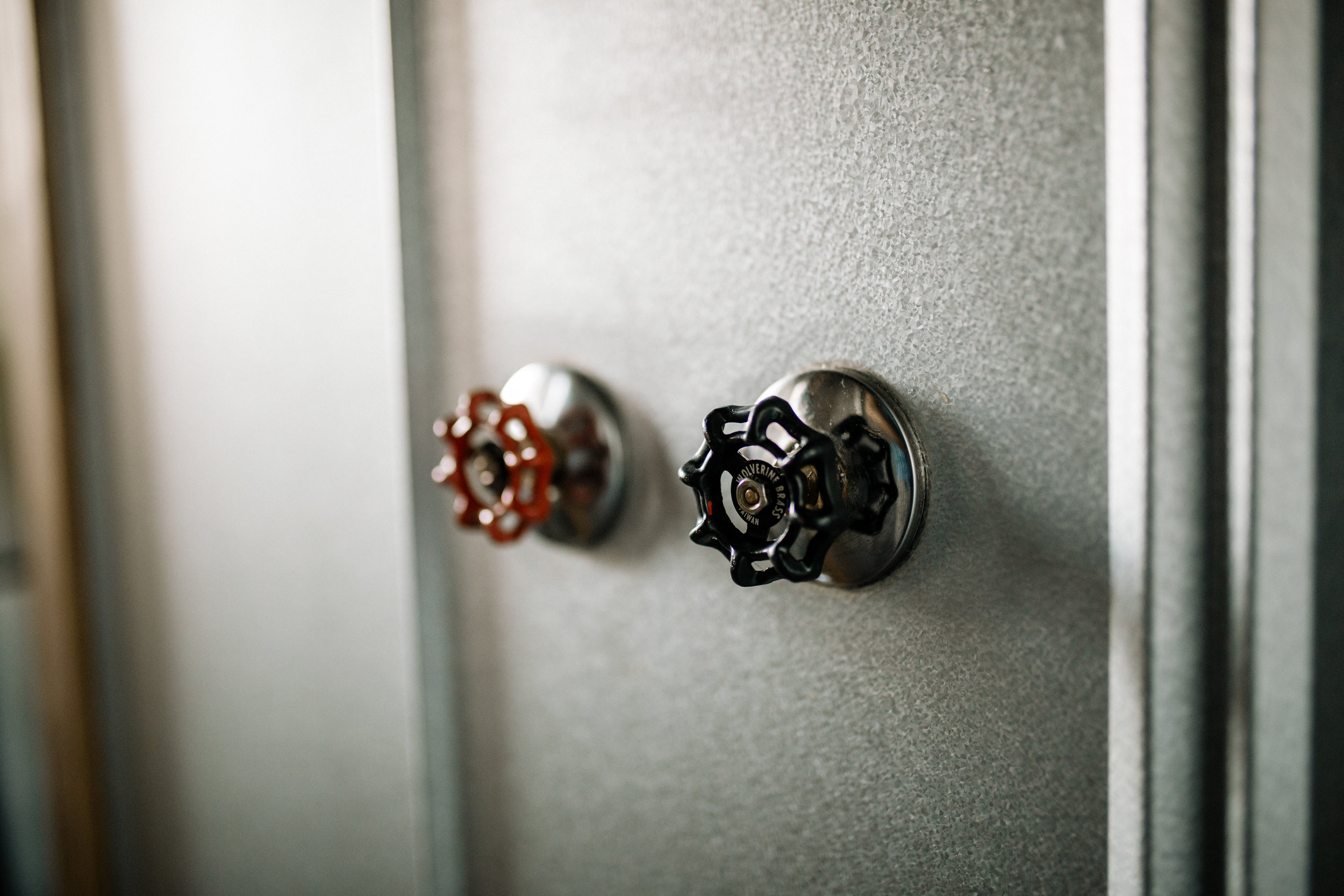 The Rook by Wind River Tiny Homes - Industrial boiler valve shower knobs.