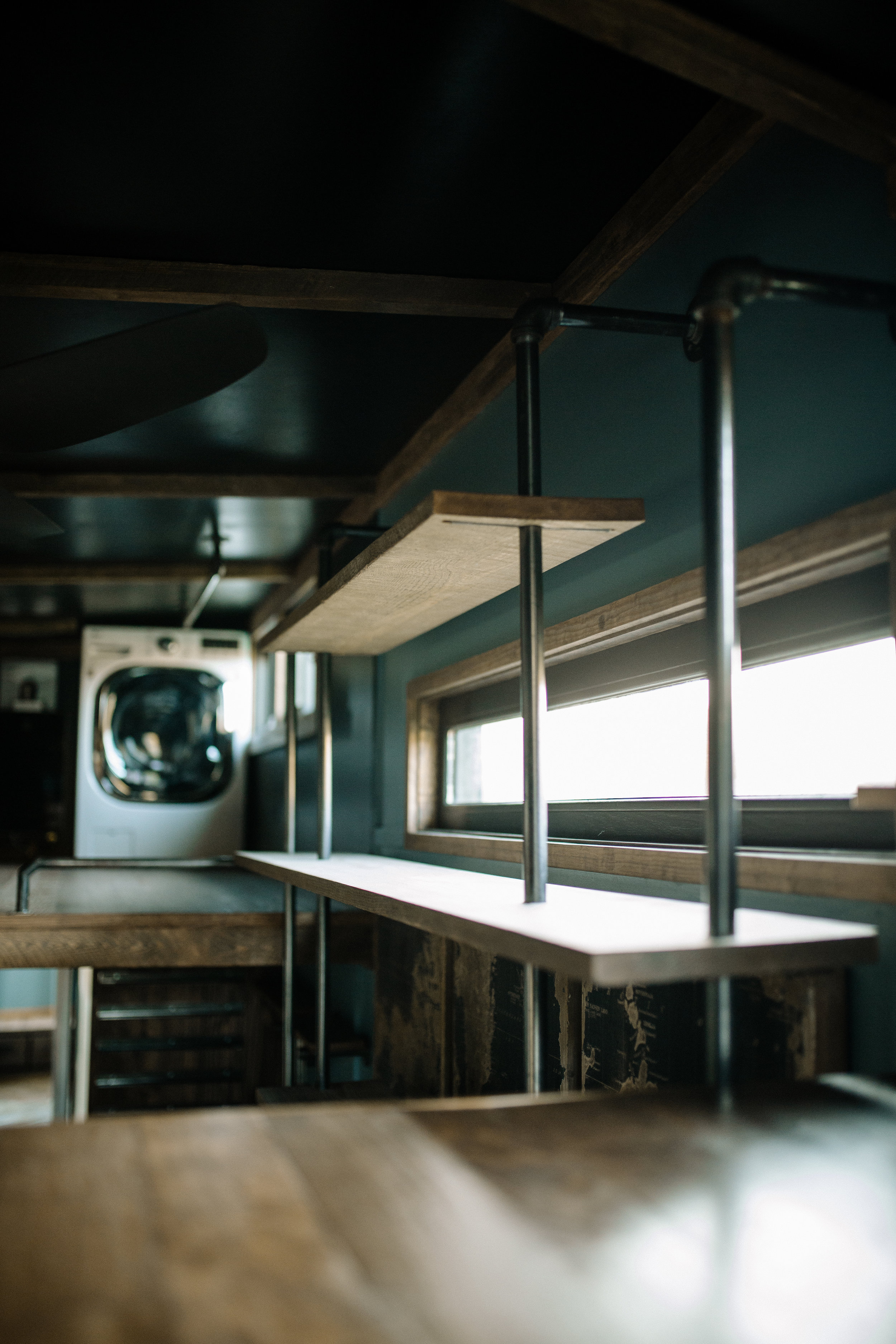 The Rook by Wind River Tiny Homes - Upper section of custom welded bookshelf with fold down desk.
