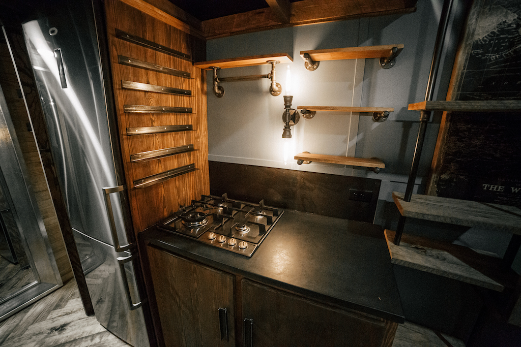The Rook by Wind River Tiny Homes - Concrete countertops, black pipe and wood open shelving, propane cooktop, raw steel spice racks.