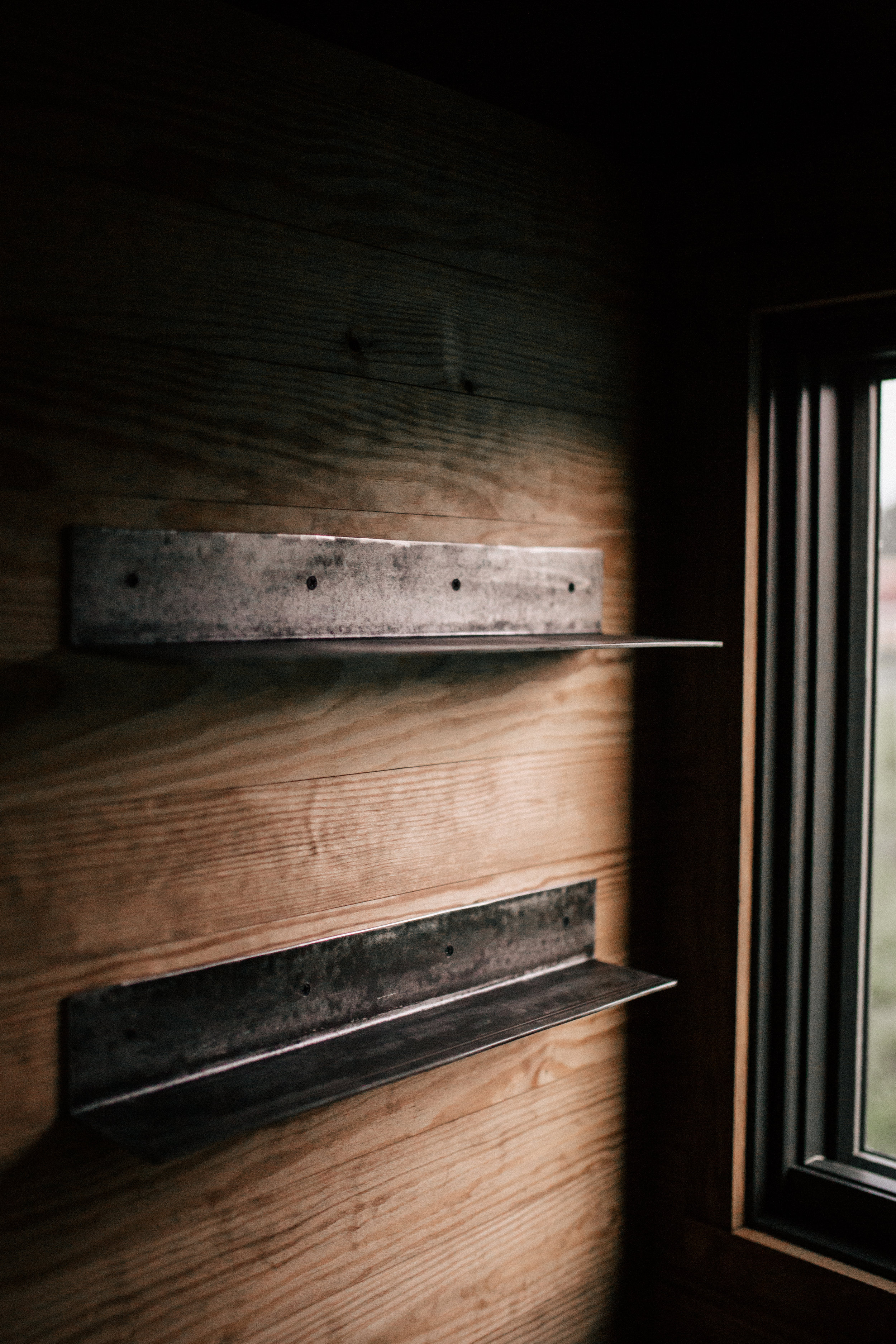 The Rook by Wind River Tiny Homes - Raw steel shelves.