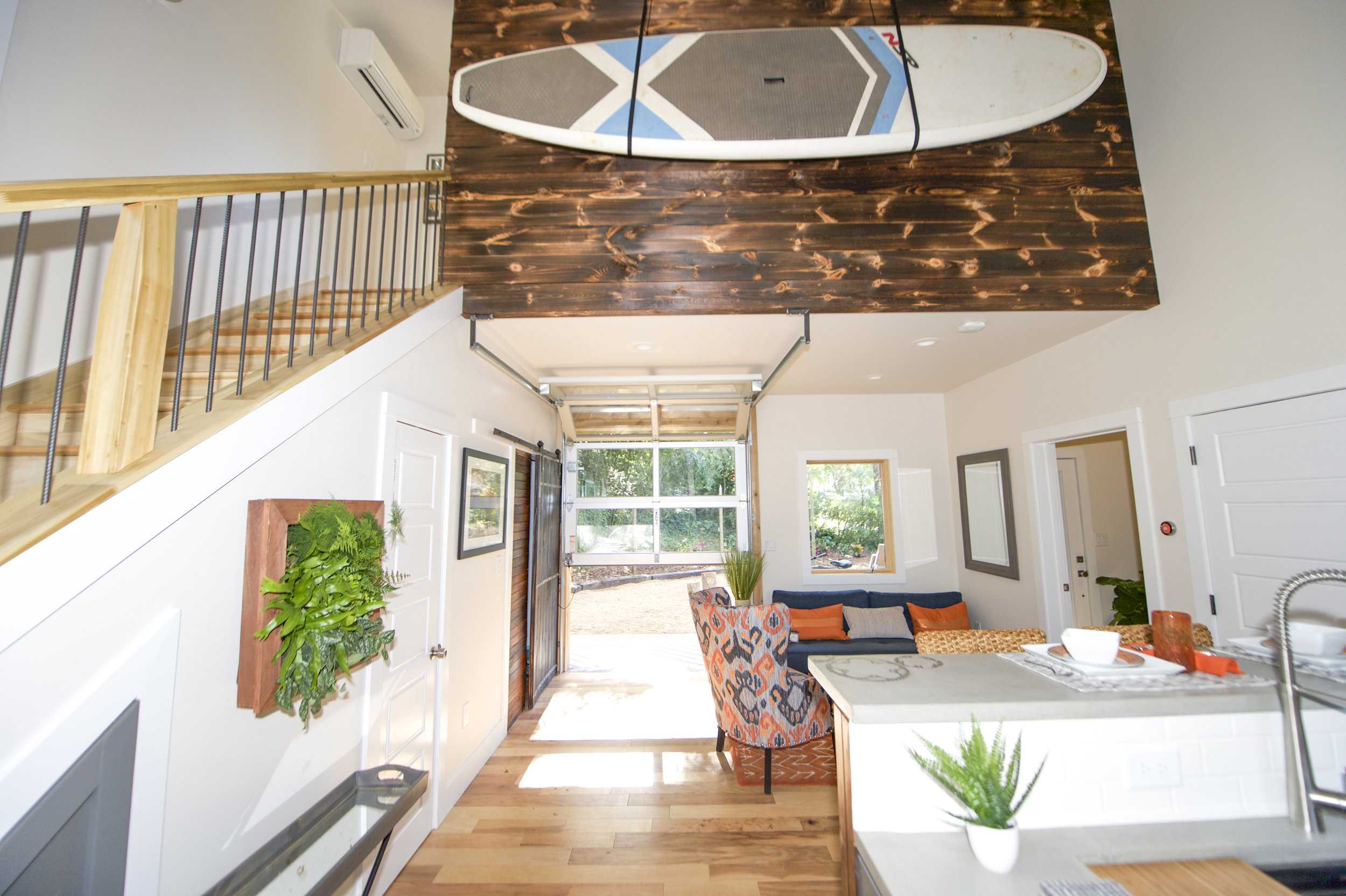 Urban Micro Home by Wind River Tiny Homes - glass garage door, stand up paddle board, rebar spindles, concrete countertops by Set In Stone, contemporary design, rustic design
