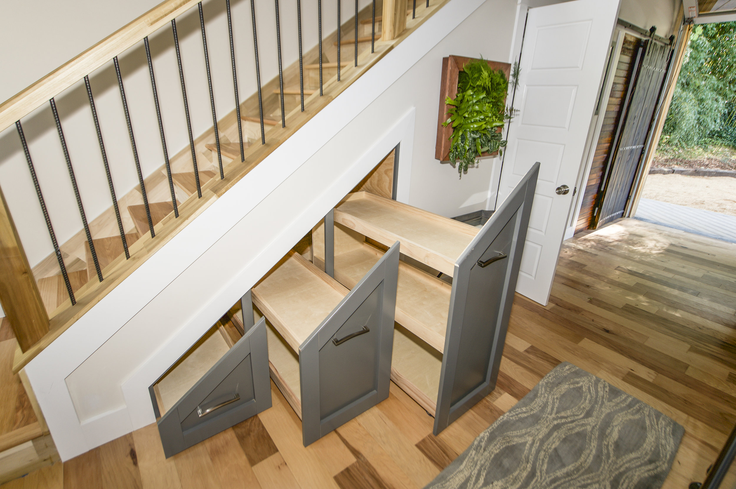 Urban Micro Home by Wind River Tiny Homes - custom pantry storage, under stair storage, pull out pantry, rebar spindles