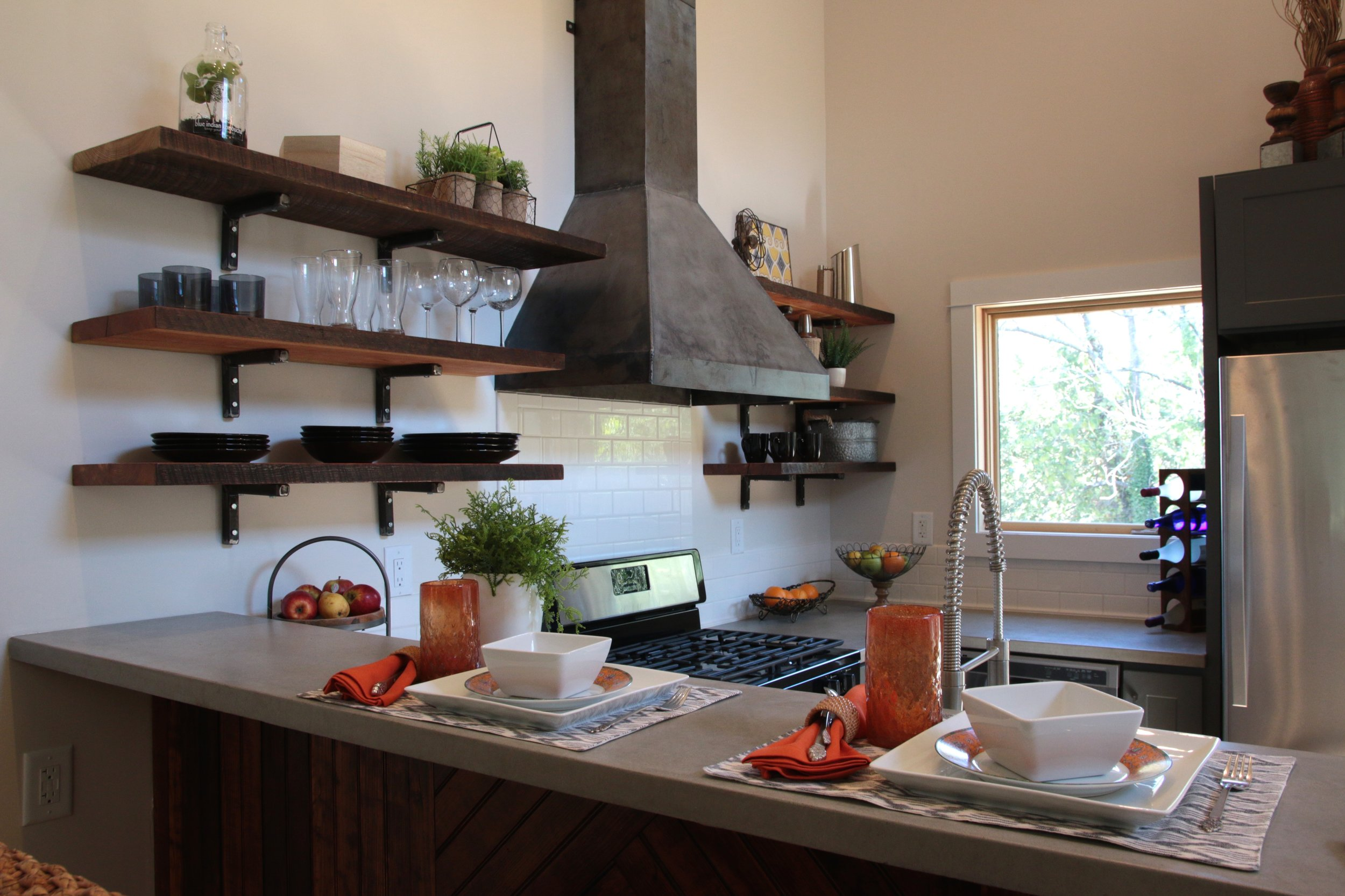 Urban Micro Home by Wind River Tiny Homes - concrete counter by Set In Stone, custom steel stove hood, Galley Workstation 4 kitchen sink, reclaimed beam open shelving