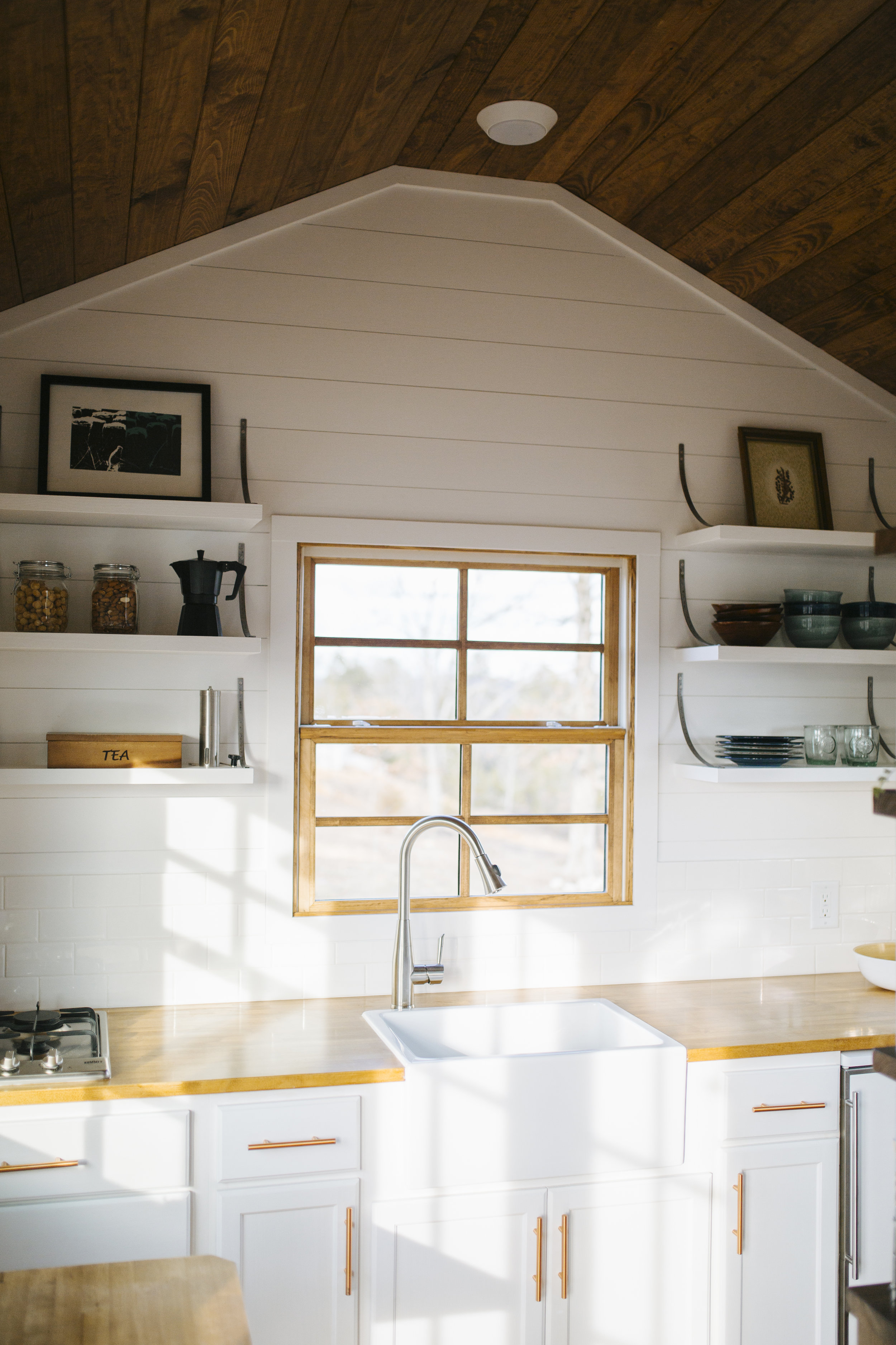 The Monocle by Wind River Tiny Homes - open shelving, custom steel brackets, farmhouse sink, butcher block countertops, shiplap siding