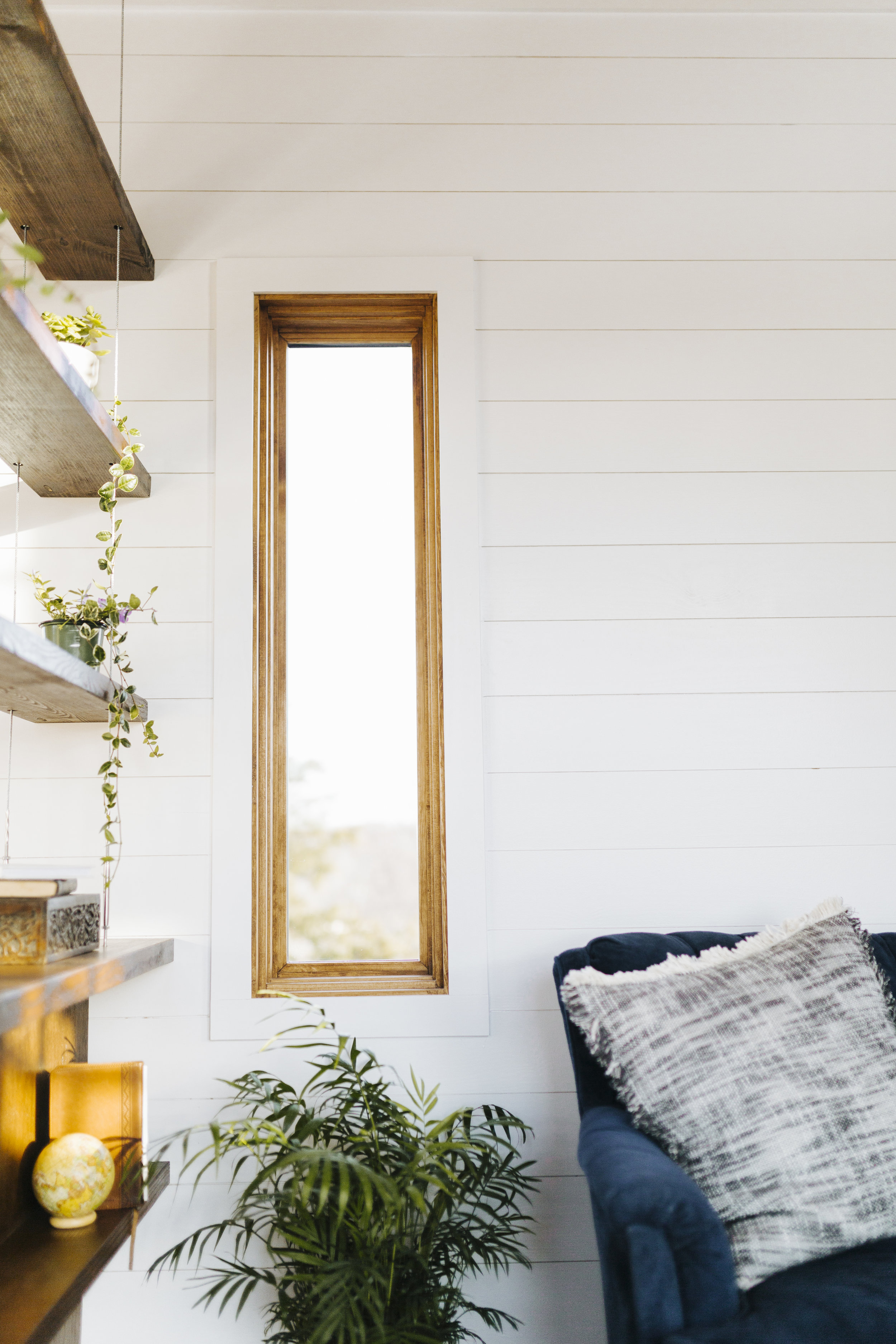 The Monocle by Wind River Tiny Homes - suspended cable shelving, shiplap siding, wood clad windows