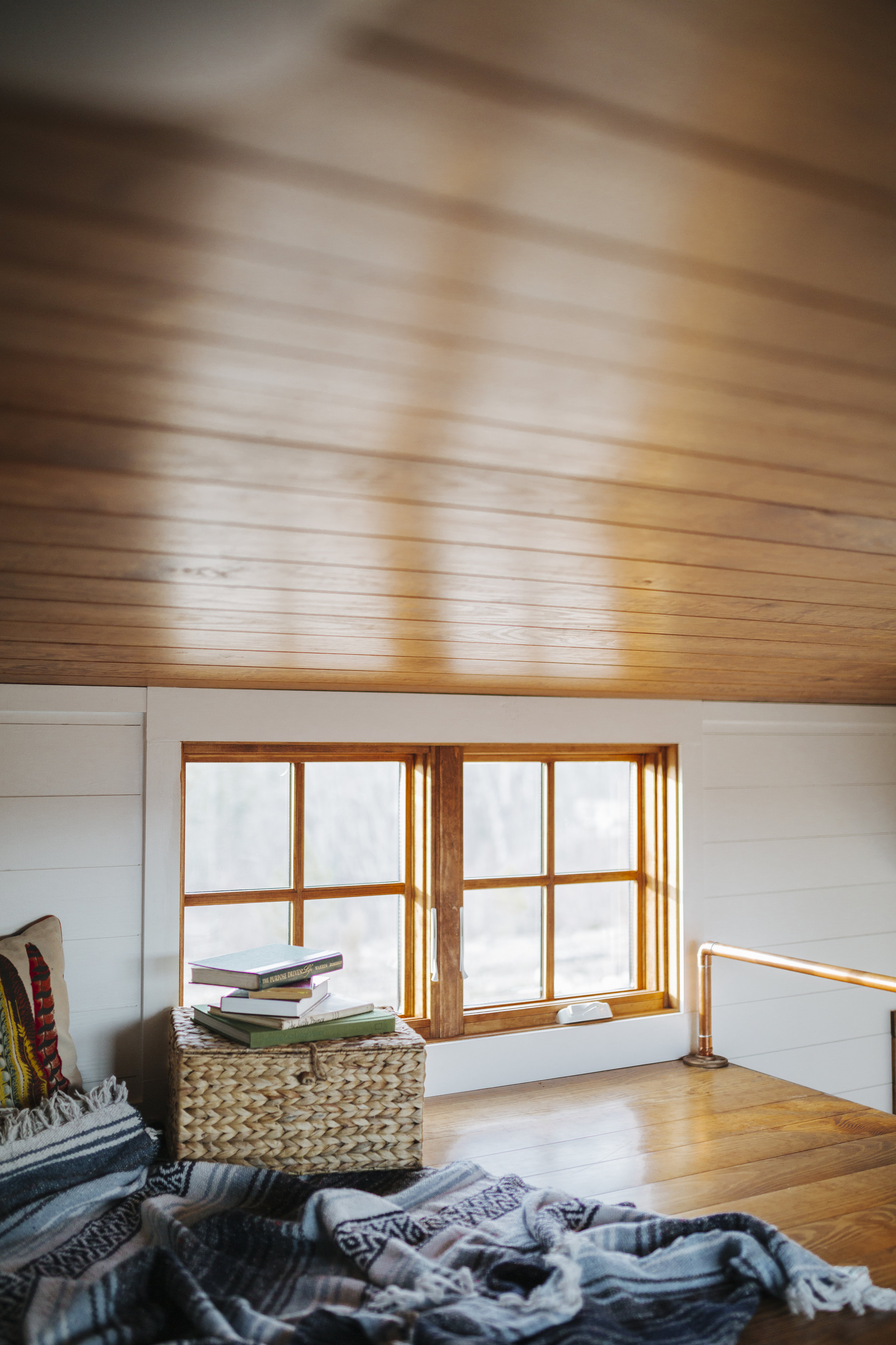The Monocle by Wind River Tiny Homes - loft, wood clad windows, custom copper railing