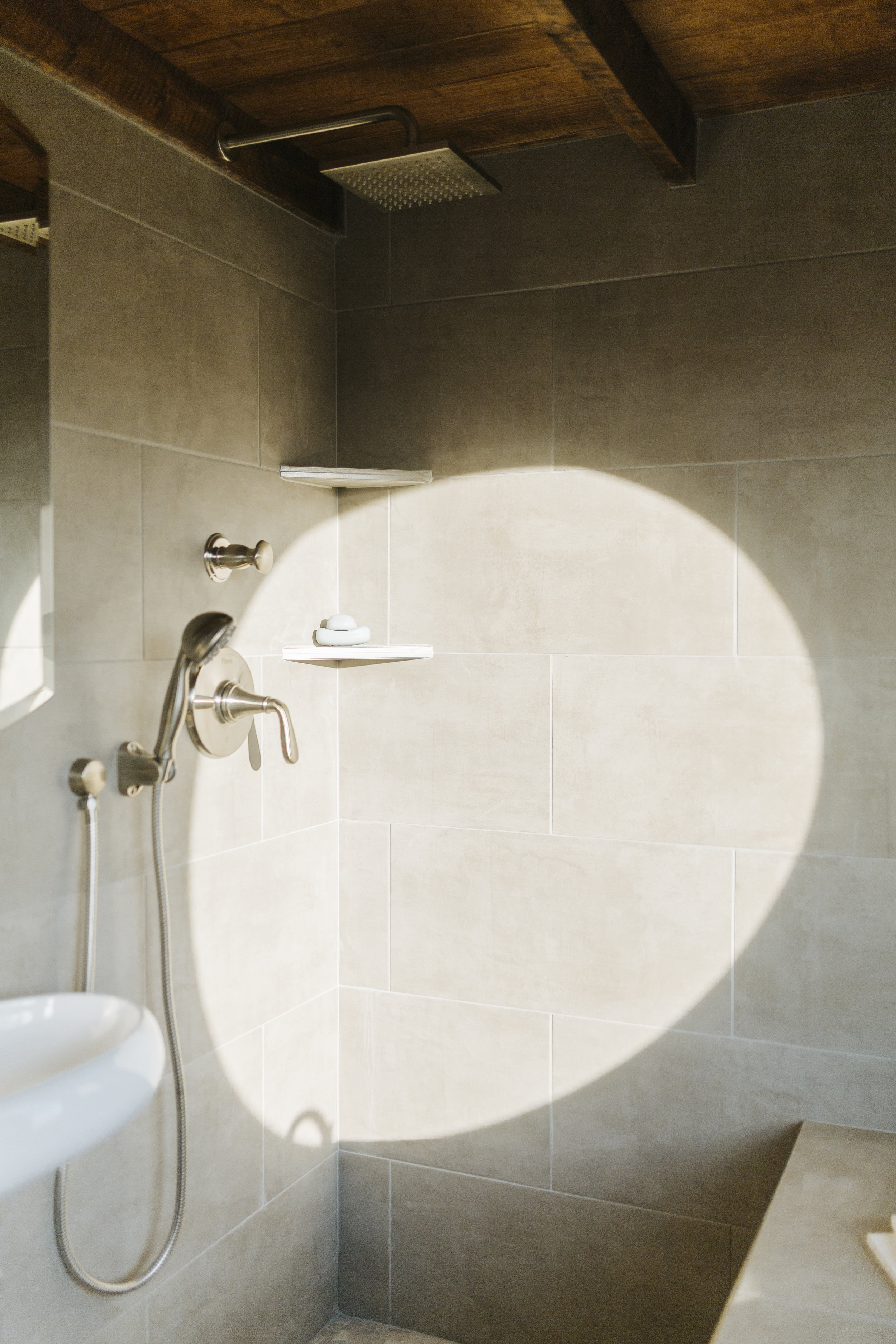 The Monocle by Wind River Tiny Homes - tile wet bath, rain shower head, hand held shower, floating sink, pebble tile floor