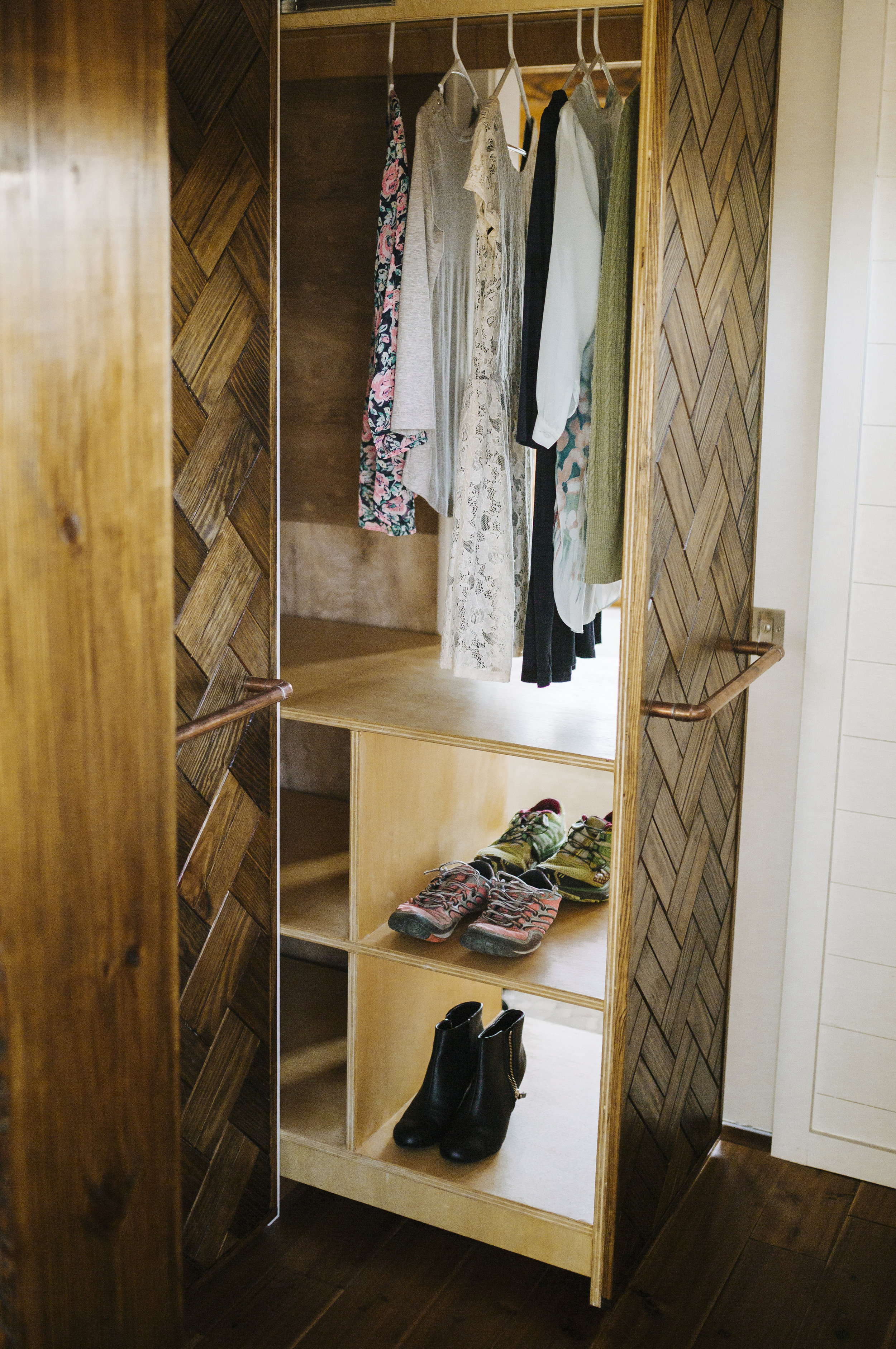 The Monocle by Wind River Tiny Homes - custom his/hers pull out closet, wood weave, copper pipe pulls