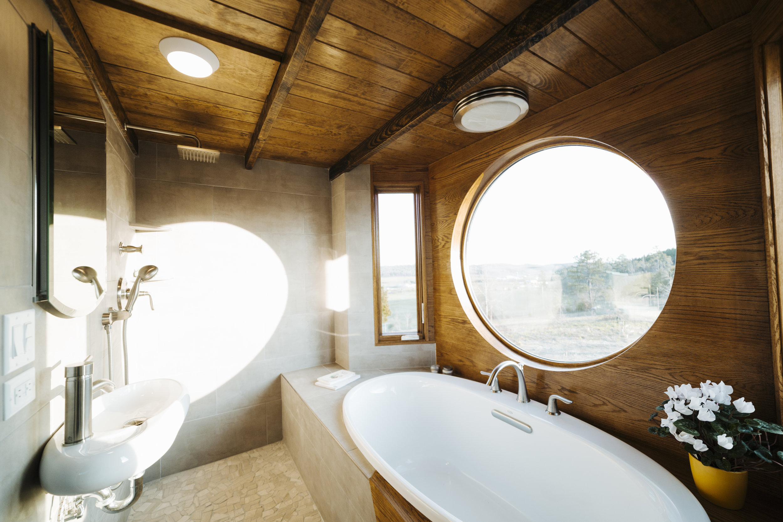 The Monocle by Wind River Tiny Homes - bath tub, wet bath, mixed tile and oak tub surround, pebble tile floor, floating sink, rain shower head, hand held shower