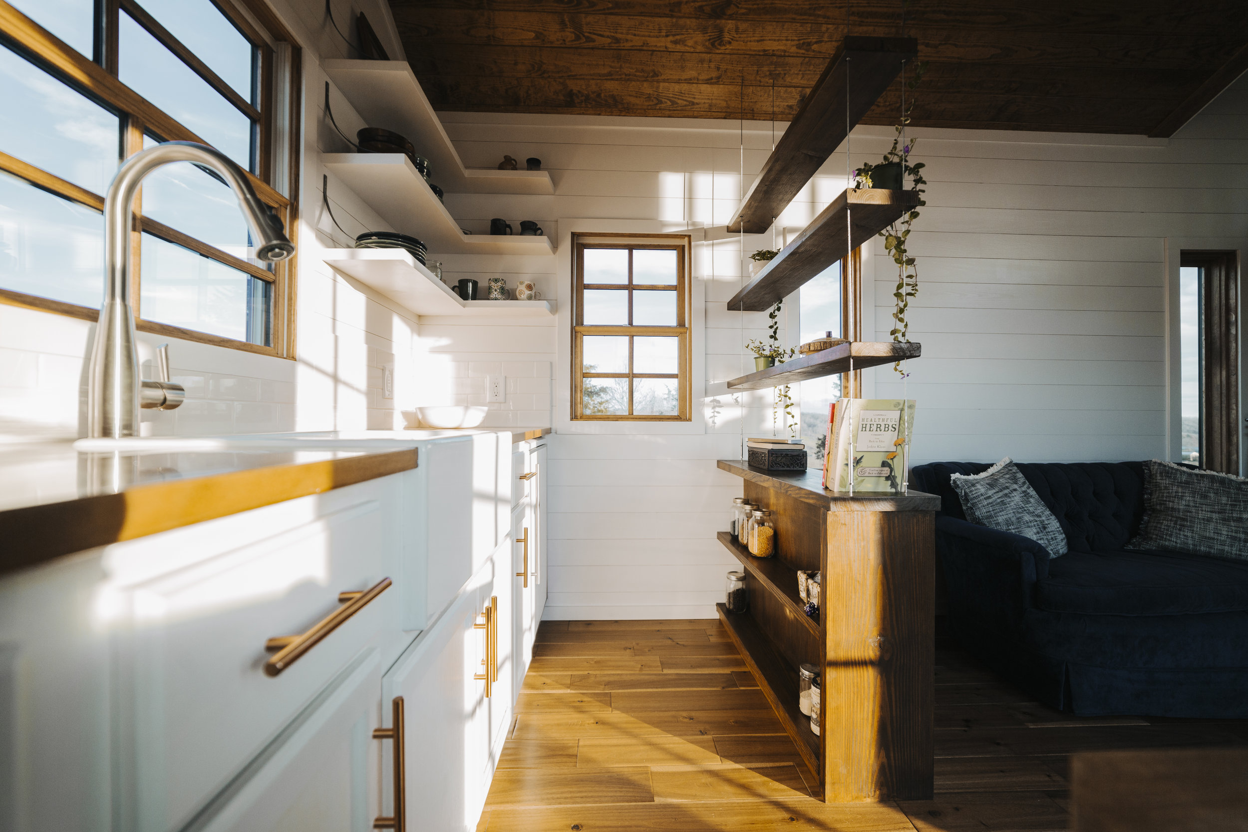 The Monocle by Wind River Tiny Homes - farmhouse sink, copper cabinet pulls, suspended cable shelving, open shelving, custom steel brackets