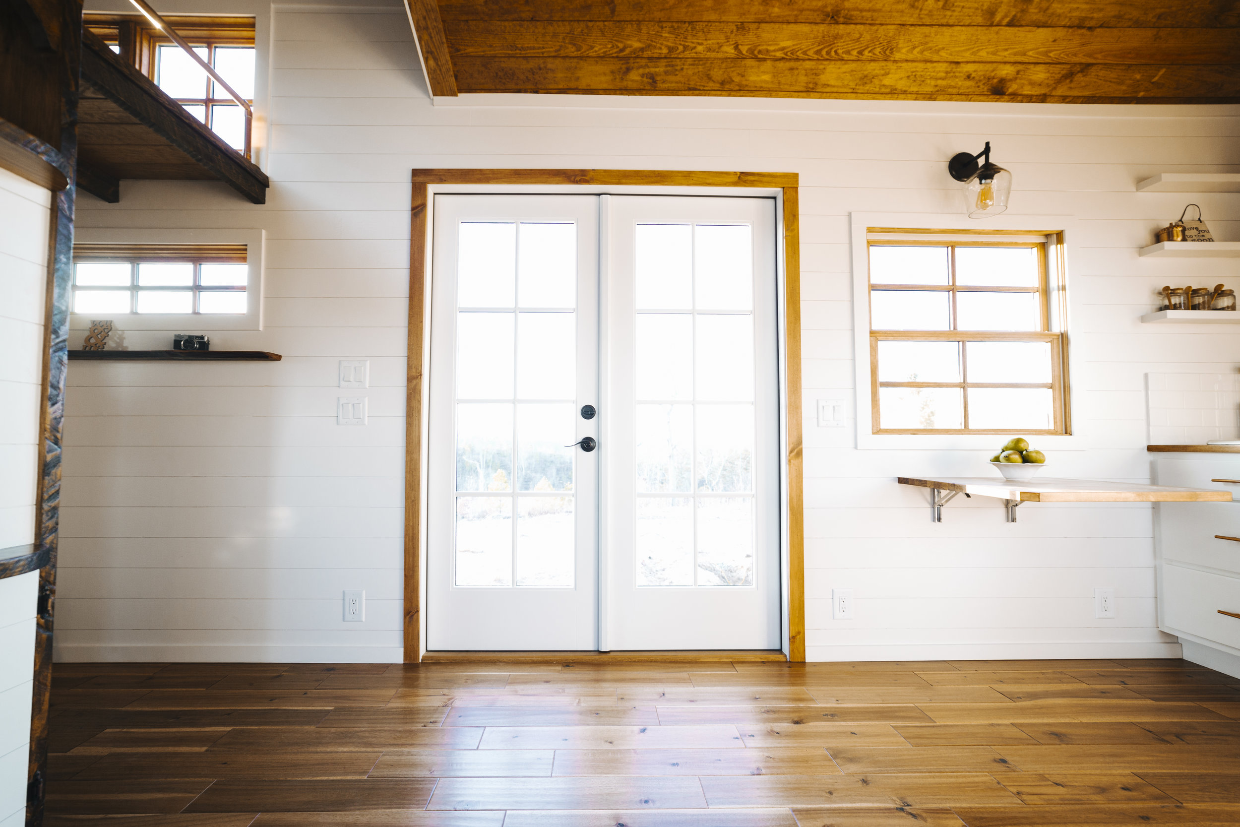 The Monocle by Wind River Tiny Homes - shiplap siding, hardwood flooring, fold down table, loft, custom copper pipe railing