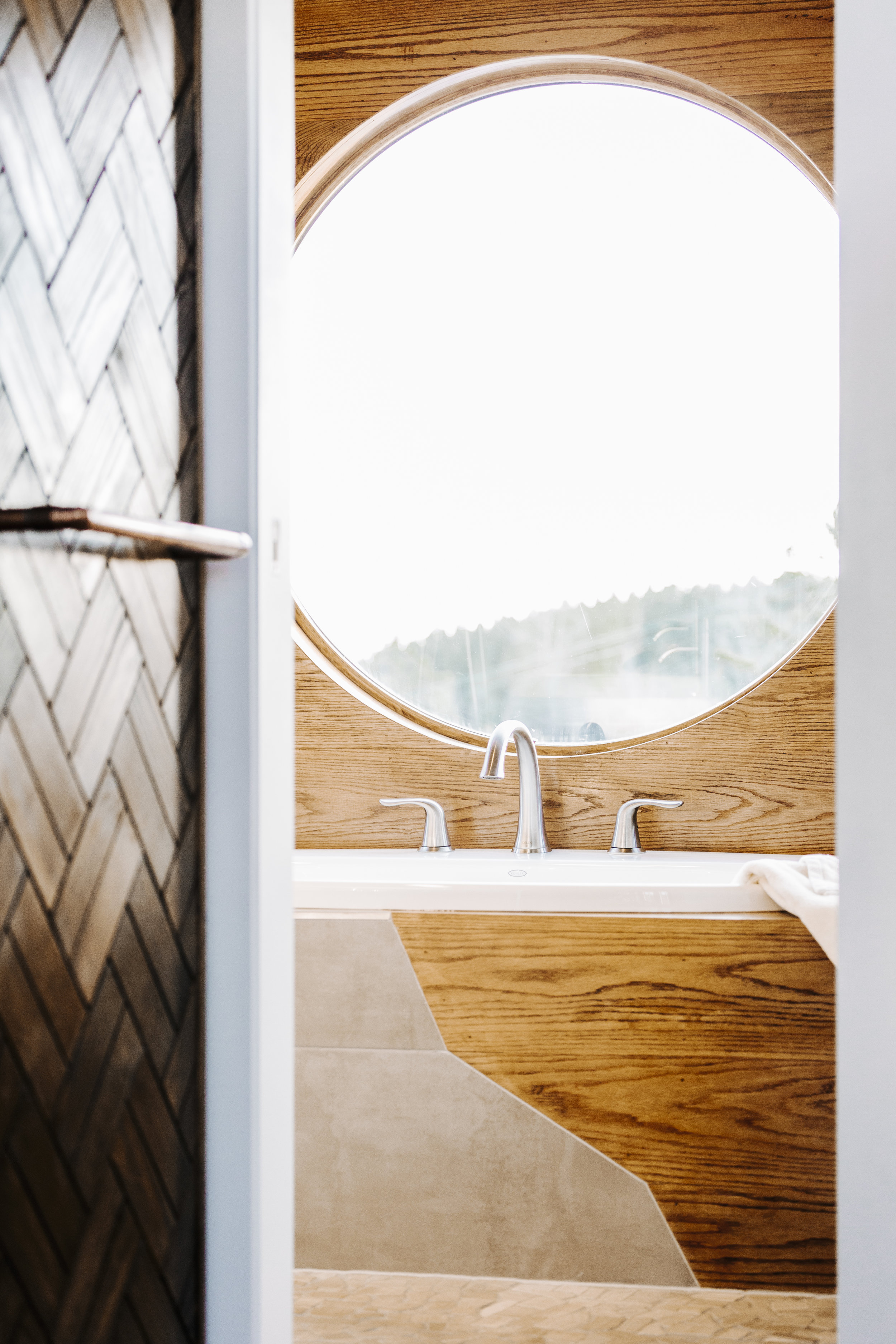 The Monocle by Wind River Tiny Homes - bath tub, mixed tile and oak tub surround, pebble tile floor, custom his/hers pull out closet, wood weave, copper pipe pulls