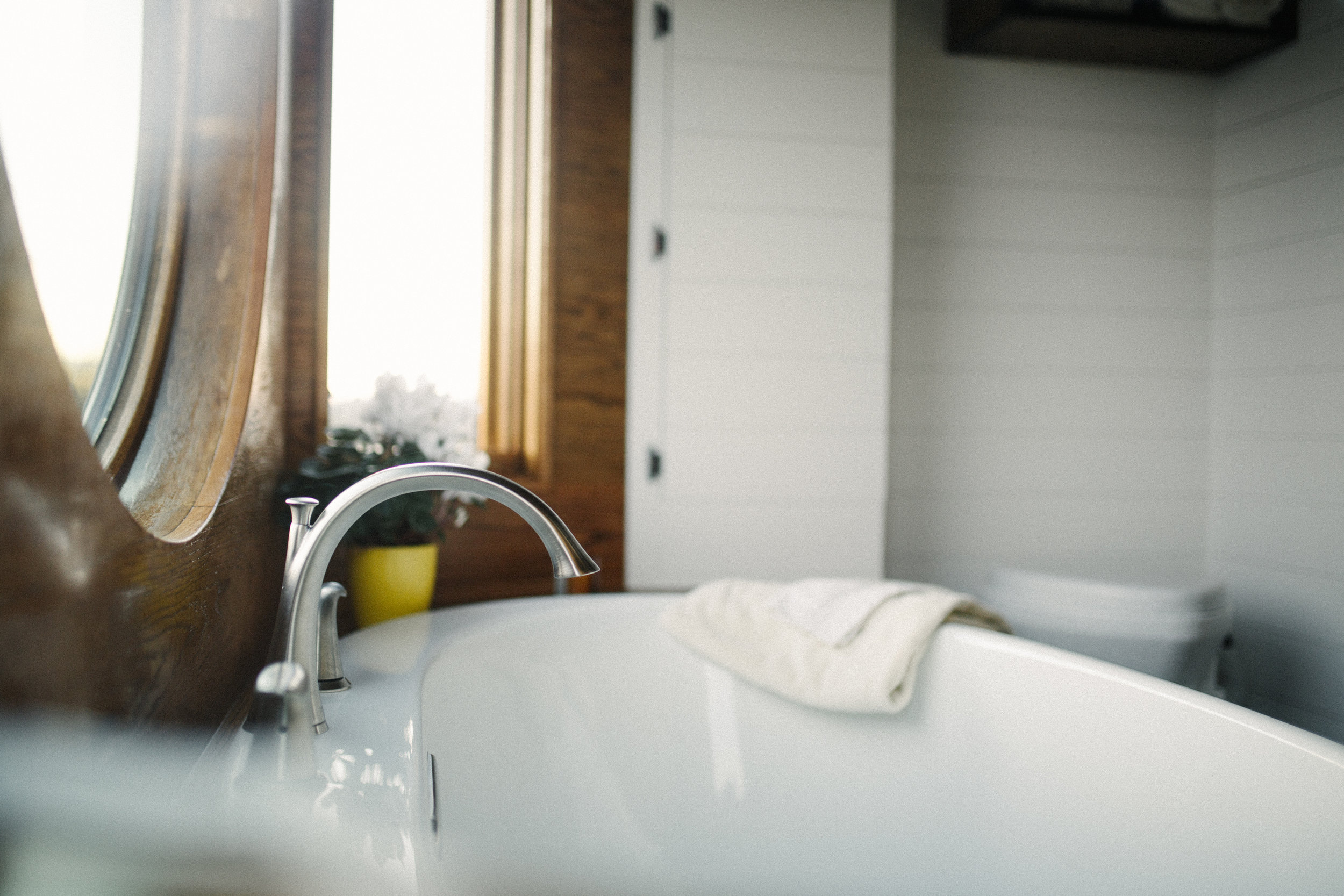 The Monocle by Wind River Tiny Homes - bath tub, wet bath, mixed tile and oak tub surround, natures head composting toilet