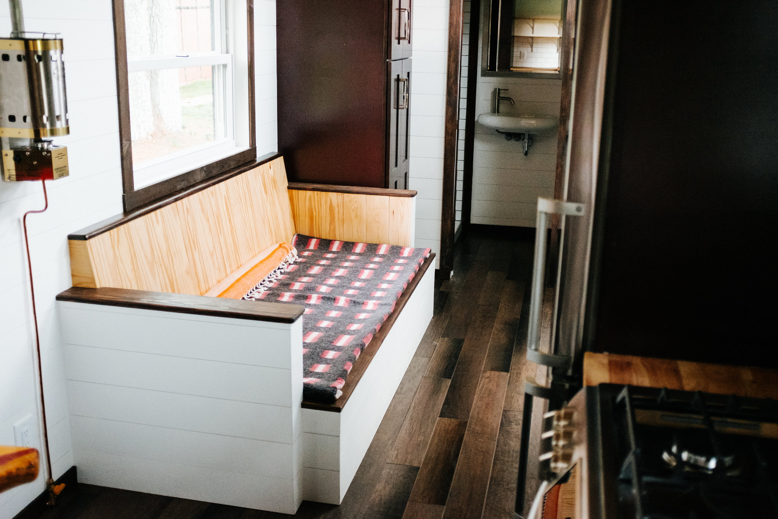 The Ironclad by Wind River Tiny Homes - custom storage couch, cozy cabin propane wall heater, ship lap
