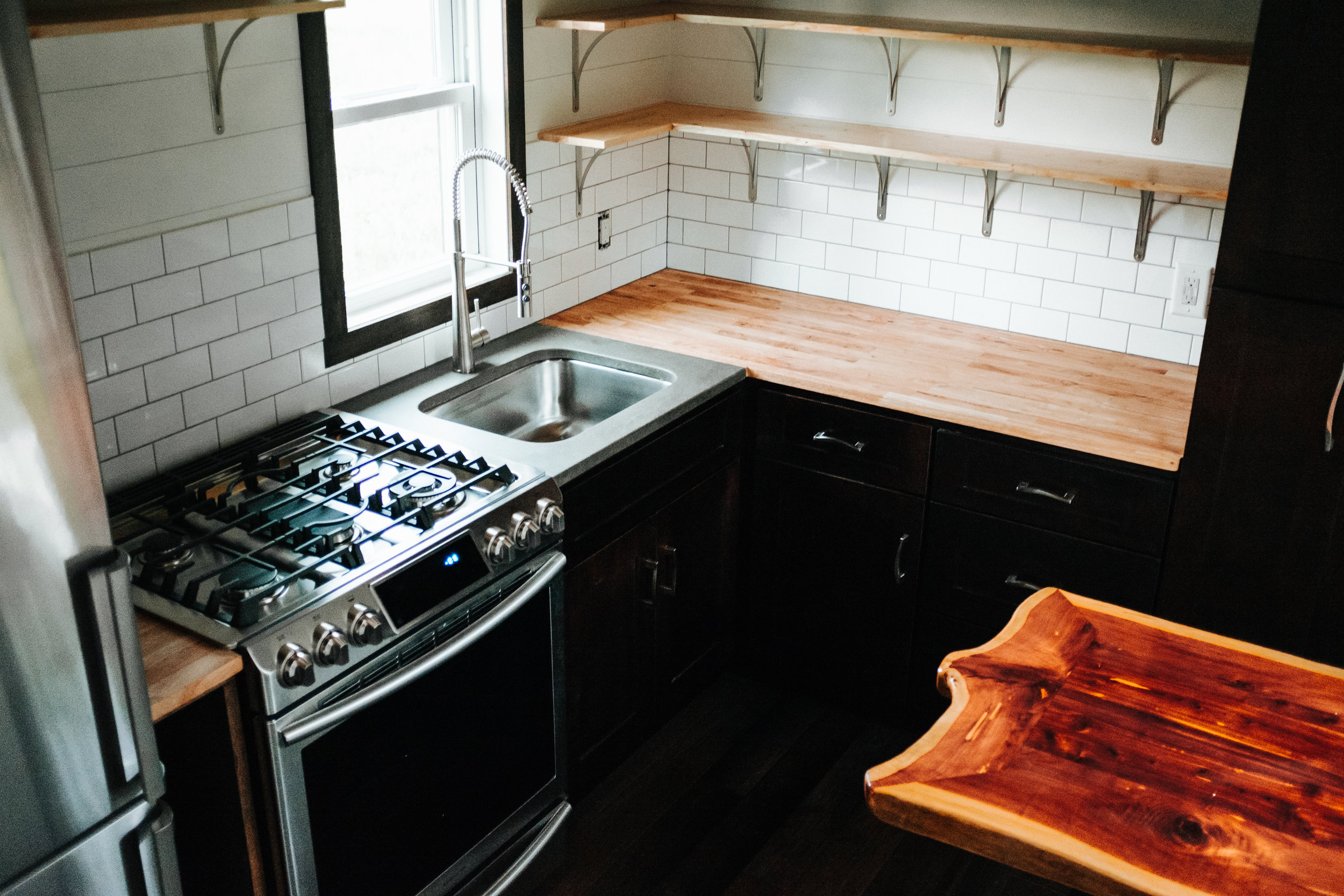 The Ironclad by Wind River Tiny Homes - shaker cabinets, subway tile, open shelving, concrete counter top, butcher block, propane range, cedar live edge table