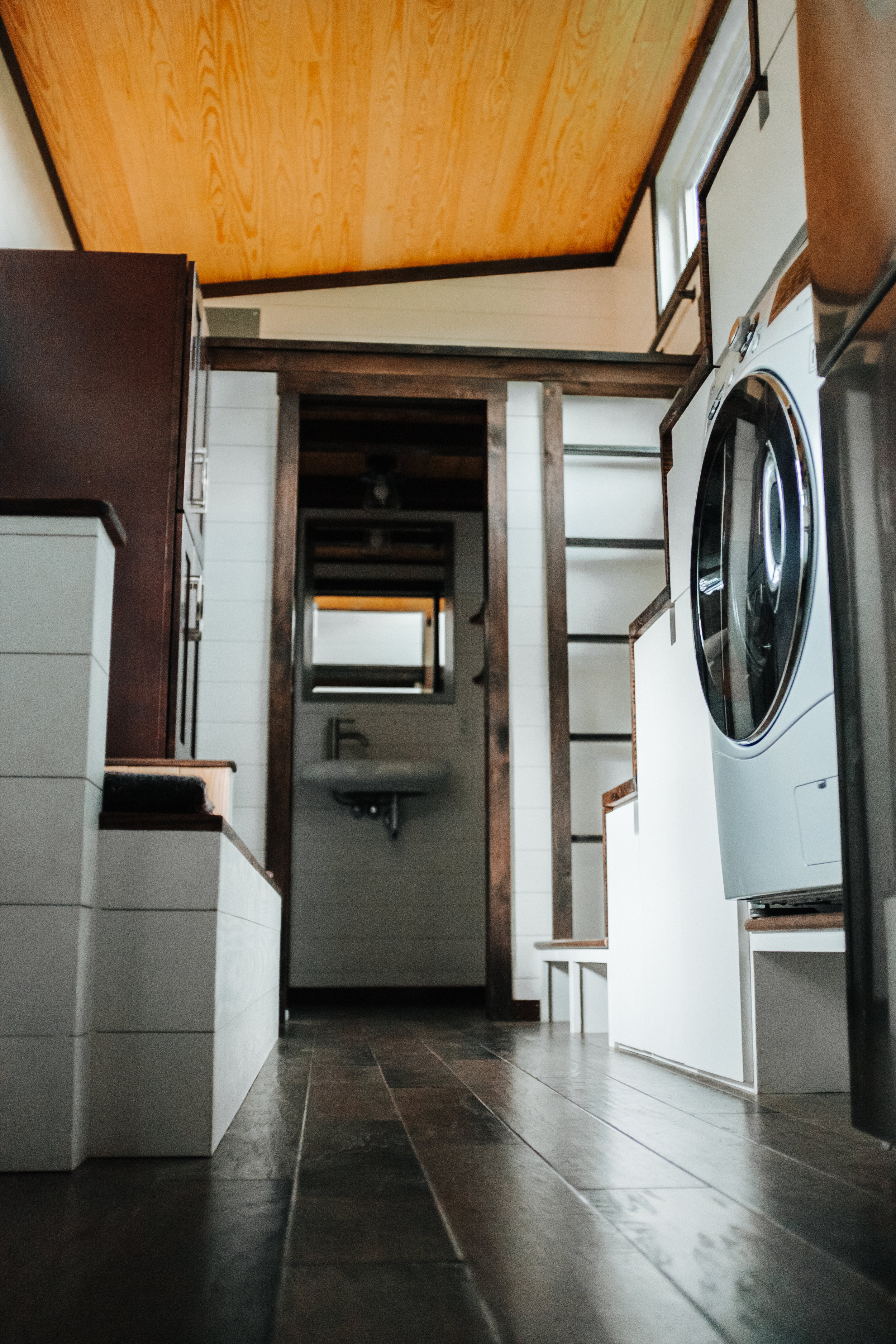 The Ironclad by Wind River Tiny Homes - washer dryer combo, custom storage stairs, built in steel ladder, ship lap, storage couch, natural pine ceiling
