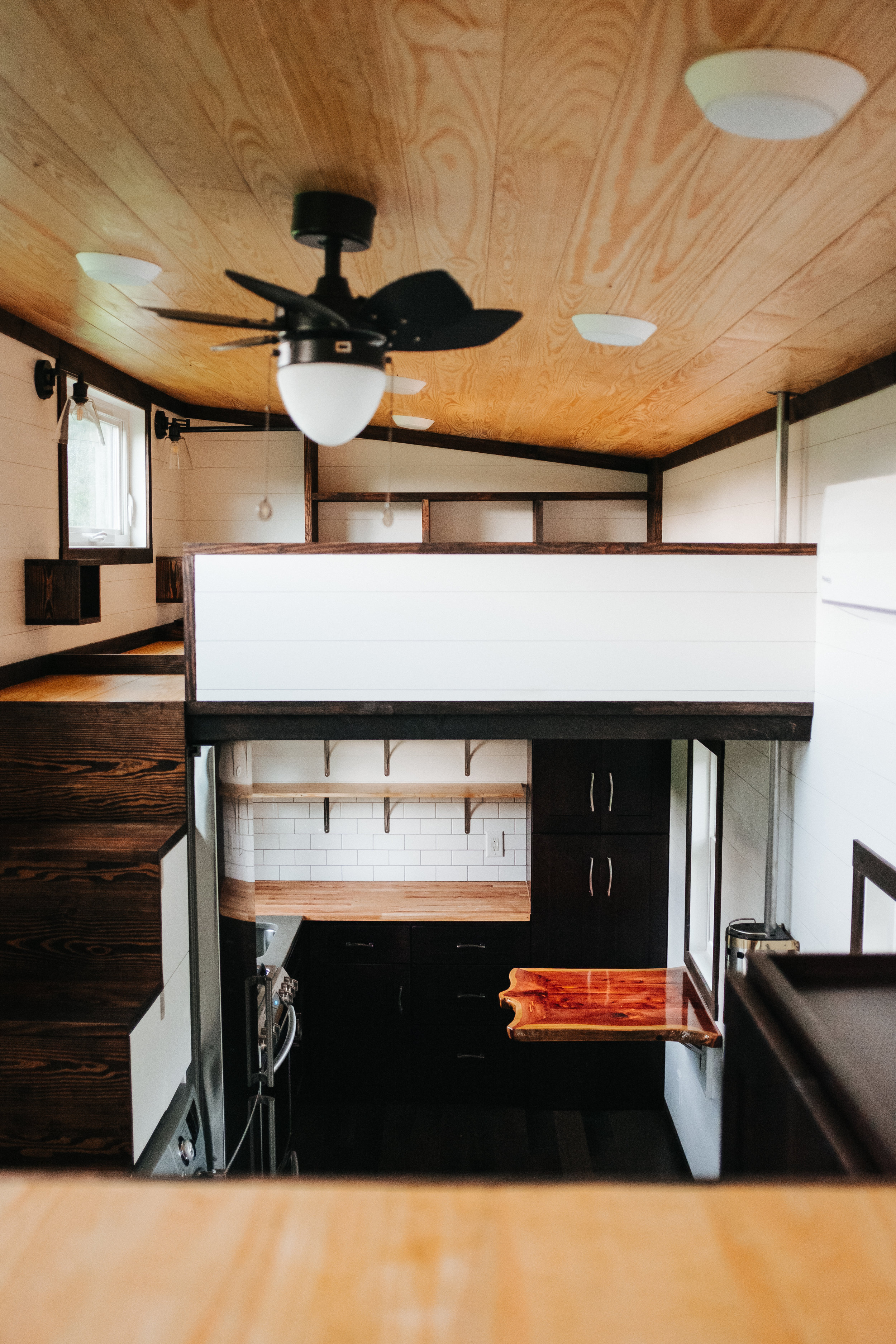 The Ironclad by Wind River Tiny Homes - custom storage stairs, shaker style closet, natural pine ceiling, ship lap, cedar live edge table